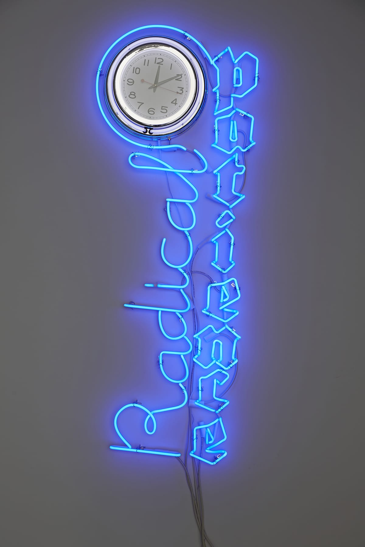 "Blue neon sign with the word ""Radical"" in cursive positioned to the left of ""Patience"" in Gothic black letter and adjacent to a white analog clock that displayed 12:10 at the time of the photo."