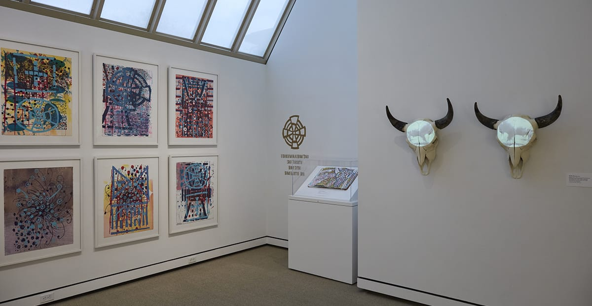 Inside gallery view with two buffalo skulls hung on the wall with looping projections of running buffalos. On the left wall, there are a series of six posters which are densely covered with colorful symbols and marks.
