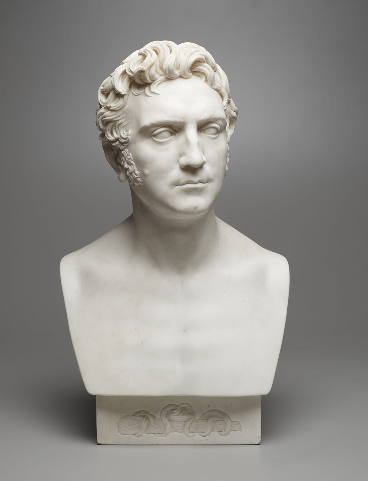 White marble bust of a male physician with swept-back hair and sideburns. Distinguishing features include a mole on his right cheek and a dimpled chin.