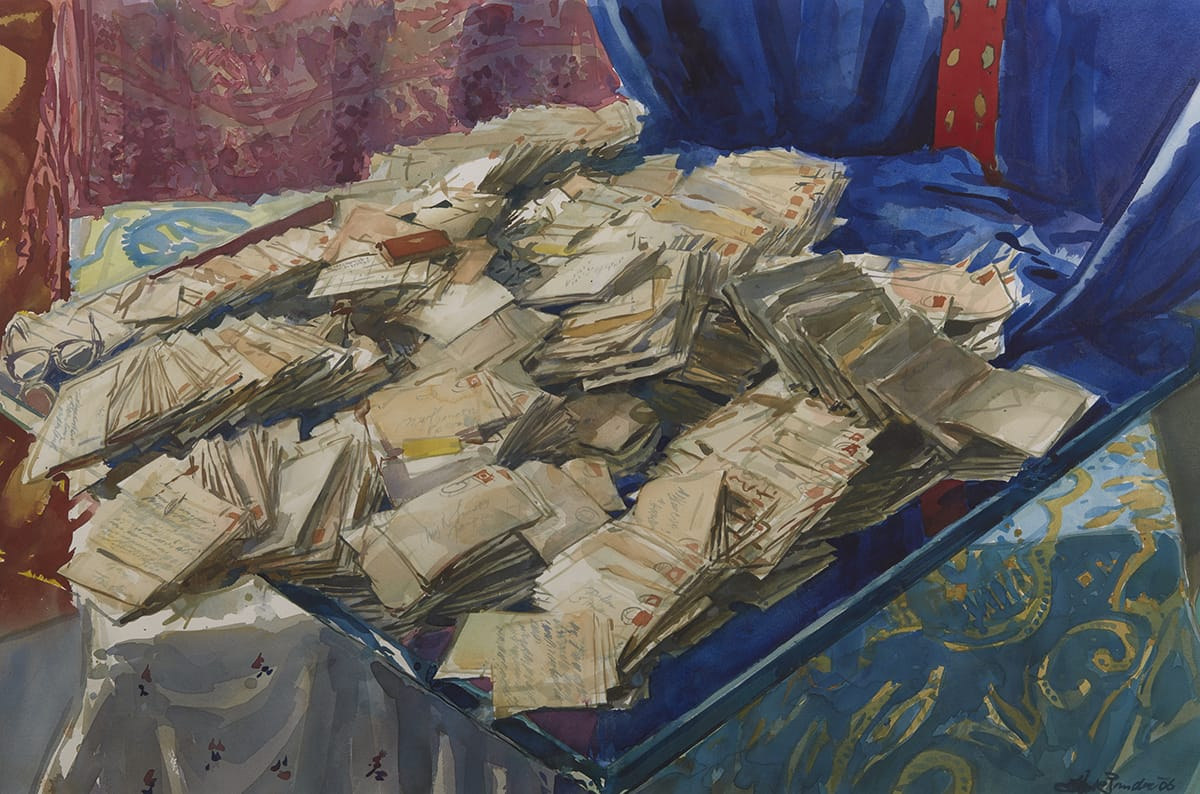 Three-quarter view of a tabletop filled with yellowed letters and envelopes against a backdrop of colorful, draped fabrics.