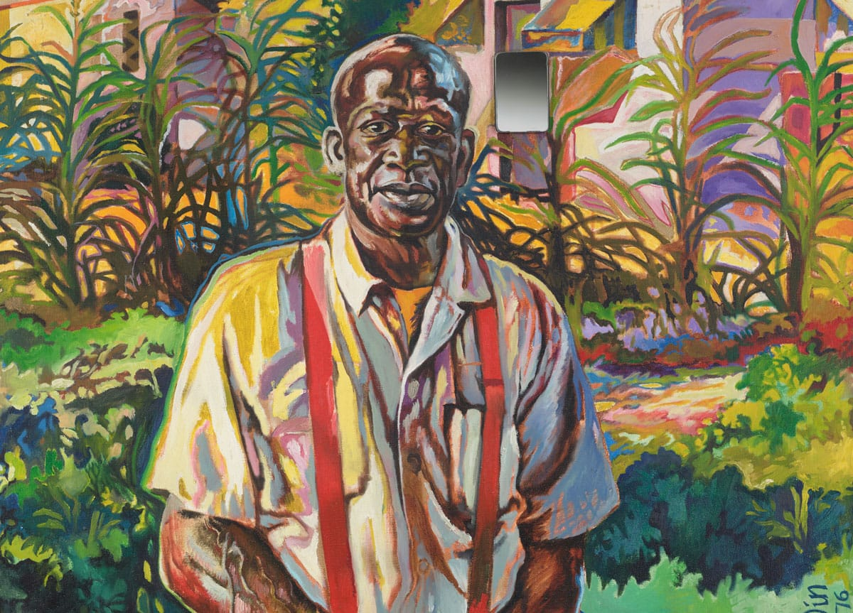 An African American man stands in the foreground with a colorfully painted garden beyond.