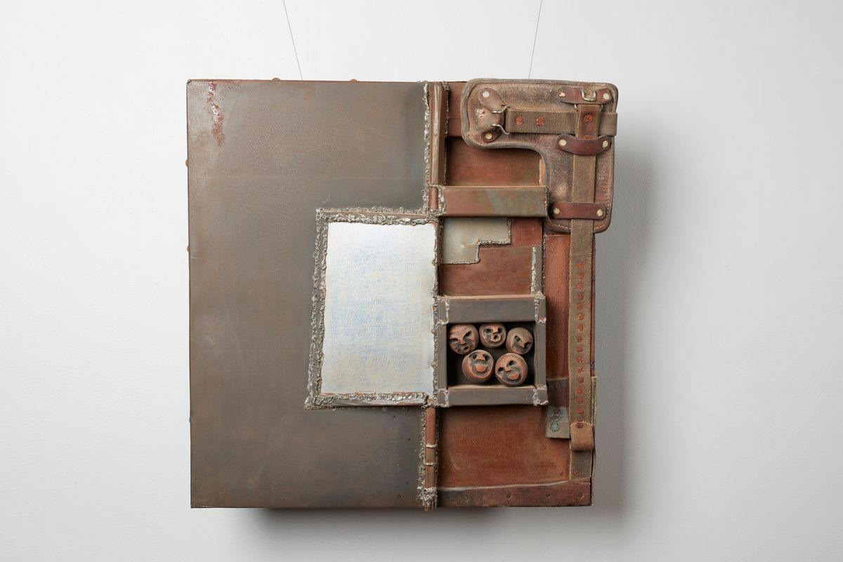 Square wall-mounted sculpture composed of mainly square and rectangle metal-looking shapes layered and soldered, creating a patchwork effect. The left half is dark grey mottled with rust color at the top edge. A vertical flat silver rectangle sits roughly in the center of the piece surrounded by jagged soldering. The right side consists of a rust-colored metal base topped with three-dimensional shapes that appear to be composed of leather strapping, more soldered metal shapes and spheres carved with faces. Dusty brown leather strapping punctuated with rivets creates an L shape starting at the top right corner running down the right edge. More riveted leather strapping continues on the bottom right edge. A metal box containing five spheres with faces with varying expressions sits two-thirds from the top of the sculpture touching the center line that divides the piece. Facial expressions include two smiling, one grimace, and two with what appear to be O-shaped mouths. Rough soldering creates thick L shapes in rust and gray above the box of spheres.