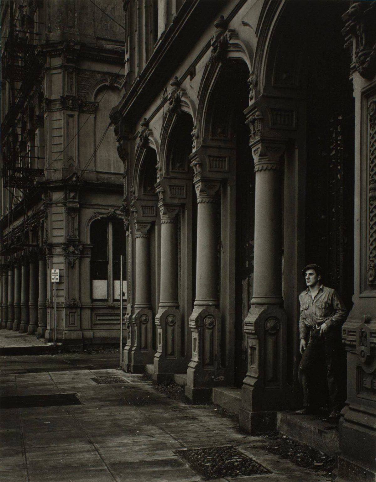 This street scene is a vertically oriented image in a range of gray tones from very light to very dark. A white man stands in the lower right of the image, leaning the right side of his body against one column of an ornate arched, colonnaded building facade while looking over a wide sidewalk at the lower left of the picture. He wears worn belted pants and shirt with a flat cap. The colonnade and sidewalk recede at a strong angle into the middle distance, ending at a side street running horizontally through the lower center left. A second building, on the far side of the cross street, fills the center left and upper left of the picture with more ornate building detail, fire escapes, and telephone wires.