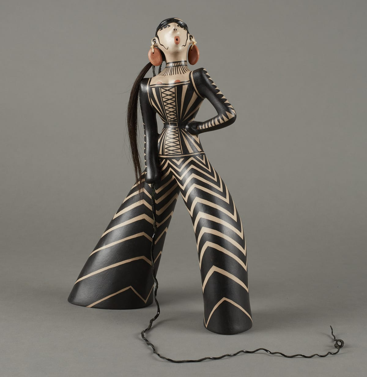 Stylized figure adorned with black-and-white triangular patterns. Details include reddish circular earrings similar to the shape of the lips, a long ponytail, and whip.