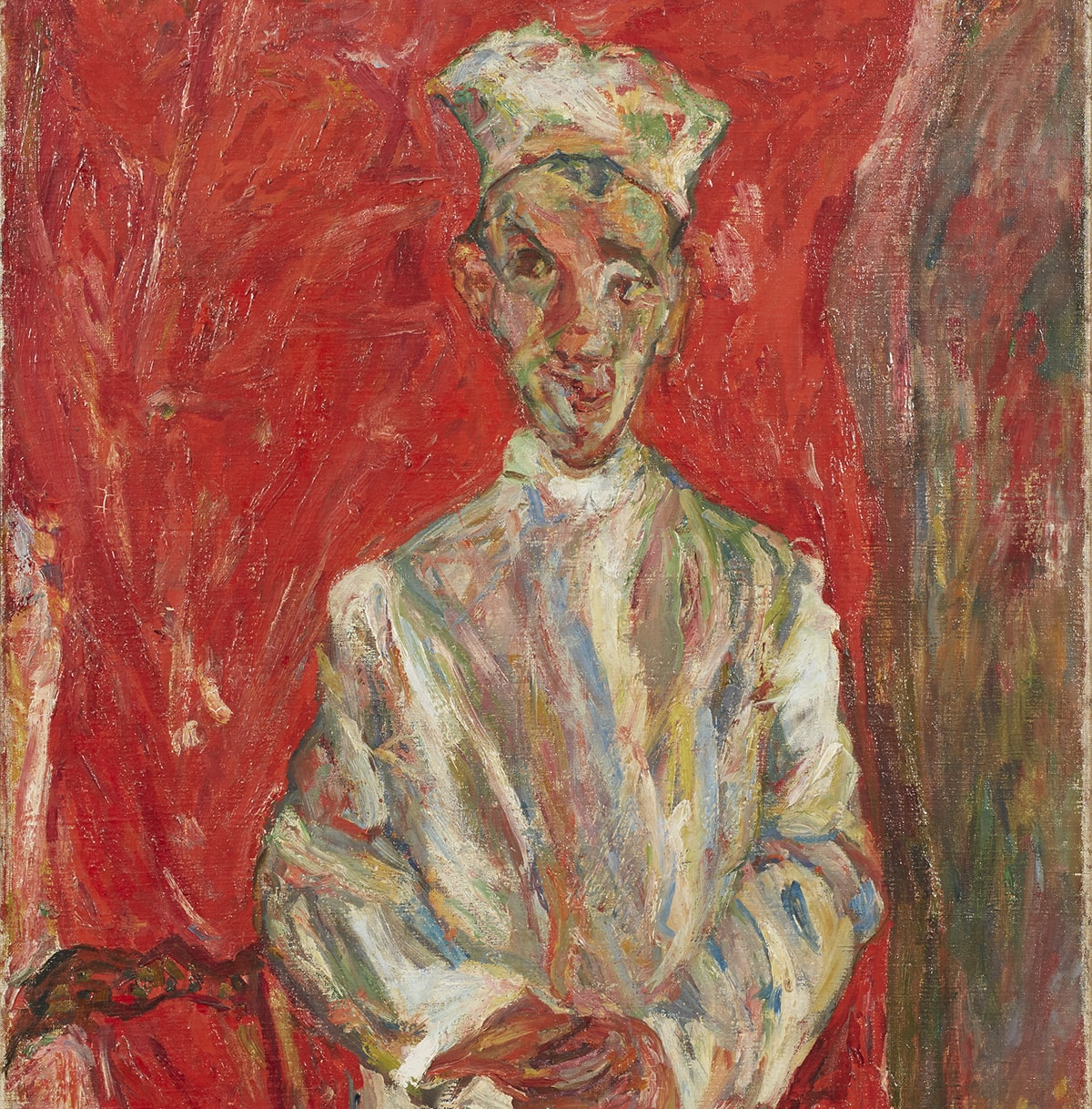 A vertical painting featuring a full-length male figure standing with his hands clasped in front. His left foot is placed in front of the other pointing to the right of the picture. He wears a cap atop a long face with a pointed chin. His ears protrude from either side of his head, bits of black hair poking out by his ears and at his forehead. Large dark eyes look off to the viewer's left. He wears what appears to be a long-sleeve, high-collared white shirt. When examined more closely, the white shirt as well as his cap and shoes are made up of many colors in addition to white—grays, blues, green, yellows, tan, orange, and dashes of red applied in broad, rough brushstrokes. Similarly, his baggy, brownish pants are painted with strokes of brown, black, yellow, red, orange, and tan. To the left of the figure stands a brown chair with ornate slatted back. Behind the figure is a field of mottled red tones making up most of the width of the painting, suggesting a curtain. A narrow swath of reds, browns, yellows complete the right side of the painting running from top to bottom.