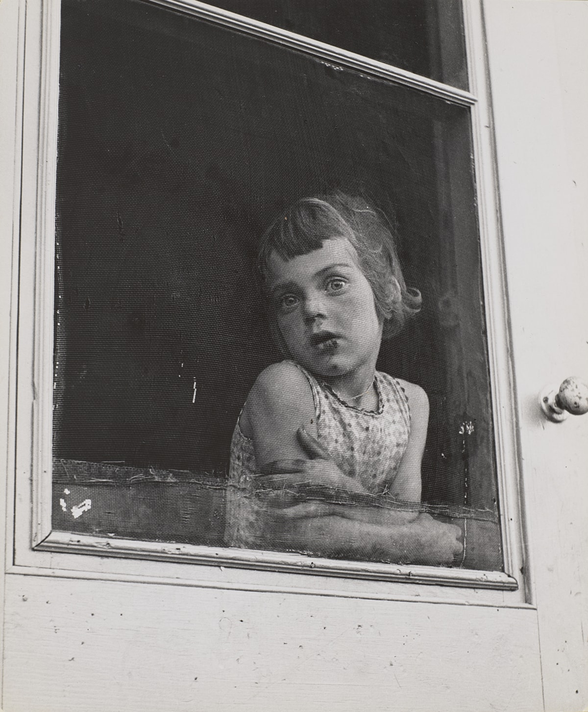 A vertical, rectangular, black-and-white photograph, featuring a young, light-skinned child at center. She leans, arms folded across her upper waist, on the inside of a patched and worn screen door, gazing through the screen and outside to the photographer/viewer. The interior space behind her is dark and without detail. The light gray door frame is seen along both the bottom and right edges of the image. A worn, chipped doorknob is on the door frame to the left of the figure at shoulder height. Her head is turned to the left, her chin touching her right shoulder. Her bobbed hair is chin-length with short, uneven bangs, and she wears a sleeveless, printed shirt. Dark areas appear on her mouth, nose and chin suggesting a scrape from a fall.