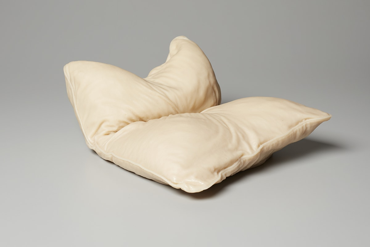 This sculpture depicts an object that resembles a bed pillow. Its shorter side is closest to the viewer. The sculpture is turned so one pillow corner is nearest the bottom center and the pillow is shown in a three-quarter view. It is deeply creased in the center as if it has been folded in half, short end to short end. The rear part of the pillow appears to be bunched upright and is indented in the center, corners jutting upward. Wrinkles, creases and piping along the seams are visible. The color is a very pale tan with cream highlights and deeper tones of tan in the creases. A shiny highlight of white is at the pillow corner nearest the viewer at bottom center.