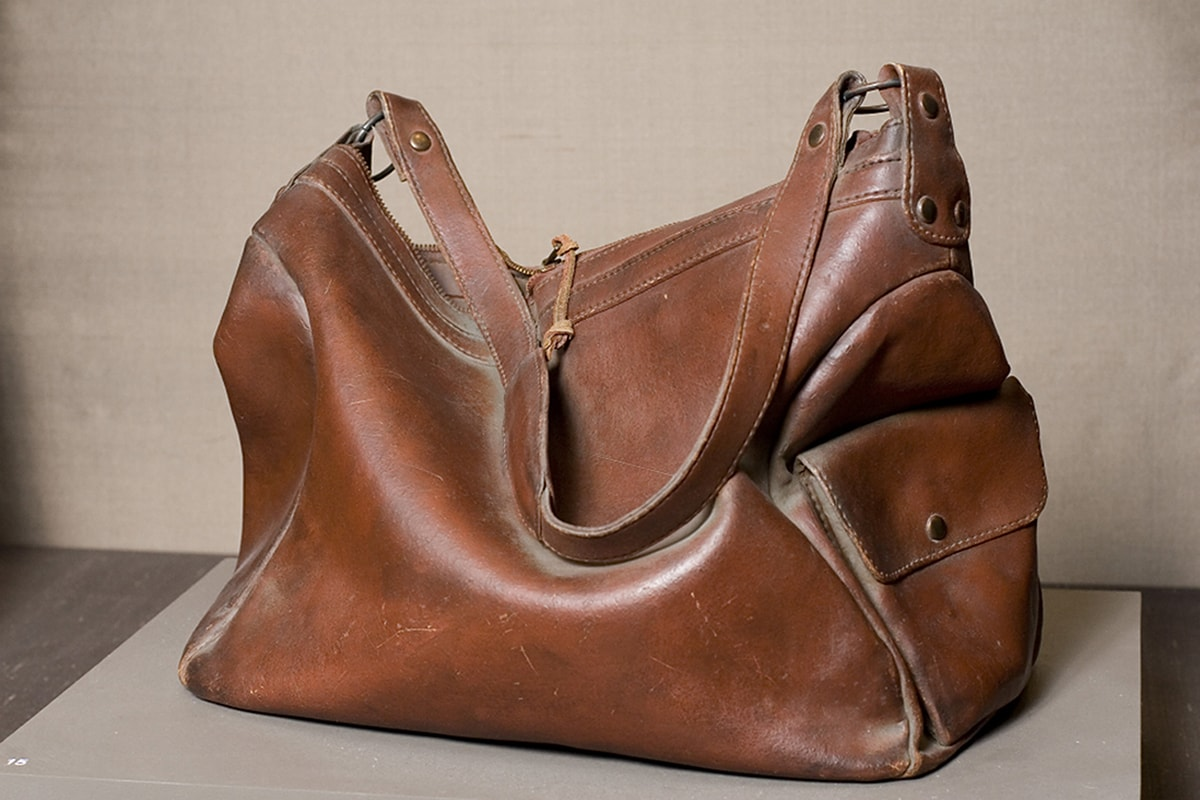 Photo of a sculpture representing a deep brown leather handbag. Viewed from the side, a rectangular handbag with both ends and middle collapse inward as if half empty. A highlight on the outward bulge of the main body of the bag is represented in a lighter color. A shoulder strap lies draped across the main body and lies next to the highlight. Hardware and rivets attach the strap to the main body of the bag at each end. A flat pocket with a flap is on the right end of the bag. Seams and stitching are clearly visible and a zipper puller is at the top center of the bag.