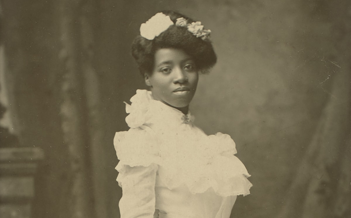 "A black-and-white photograph of a young African American woman standing turned to the right in a three-quarter view, head facing forward, gazing directly at the viewer. She wears a white, floor-length gown with high neck and long sleeves. Her hair is swept up, piled on the crown of her head, and adorned with several flowers. Her expression is neutral, her head slightly tilted to the left. She holds a large, full bouquet of roses, carnations, and ferns whose long stems are tied with a ribbon. The flowers are angled down toward the floor while the stems point up and away from the viewer. The bottom of her gown ends in several tiers of ruffled flounces. Behind the figure is a painted backdrop depicting drapery and part of a stone mantel. A wide, tan border surrounds the long, rectangular portrait, showing bumped and creased corners and staining at bottom. A handwritten inscription reads: ""1st blk. graduate // from high school // in Hastings, Nebraska // about 8 yrs. before grandma Nonie"". A logo reading ""Payne Hastings, Nebr"" is printed in the bottom right corner of the border."