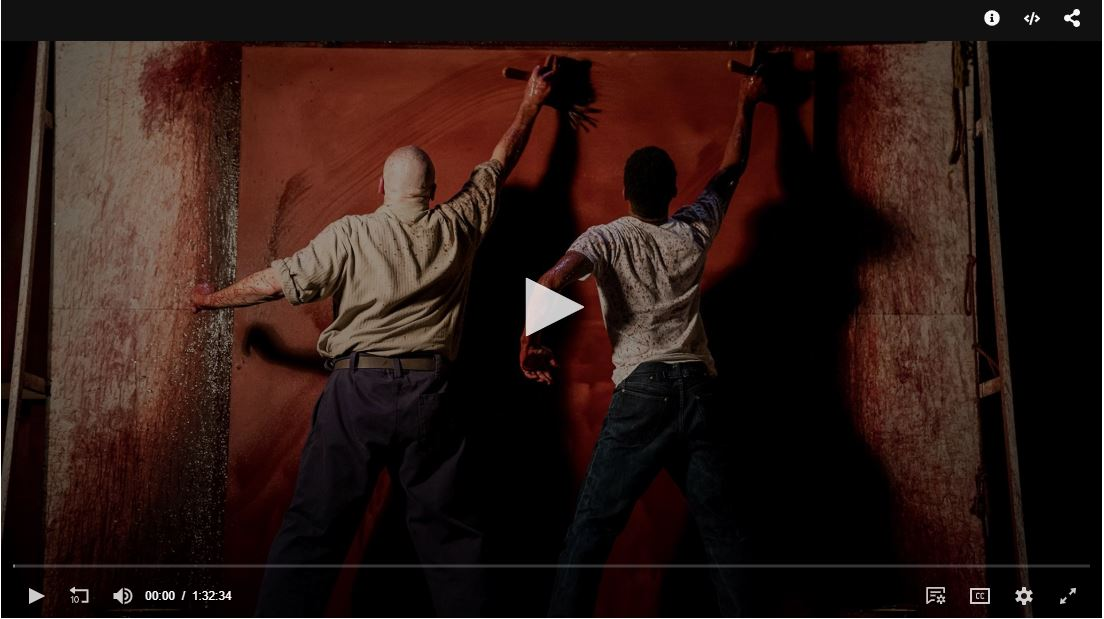 Frozen frame of video clip. One dark-skinned masculine-presenting individual and one dark-skinned masculine-presenting individual paint a large wall red with a substance that resembles blood.