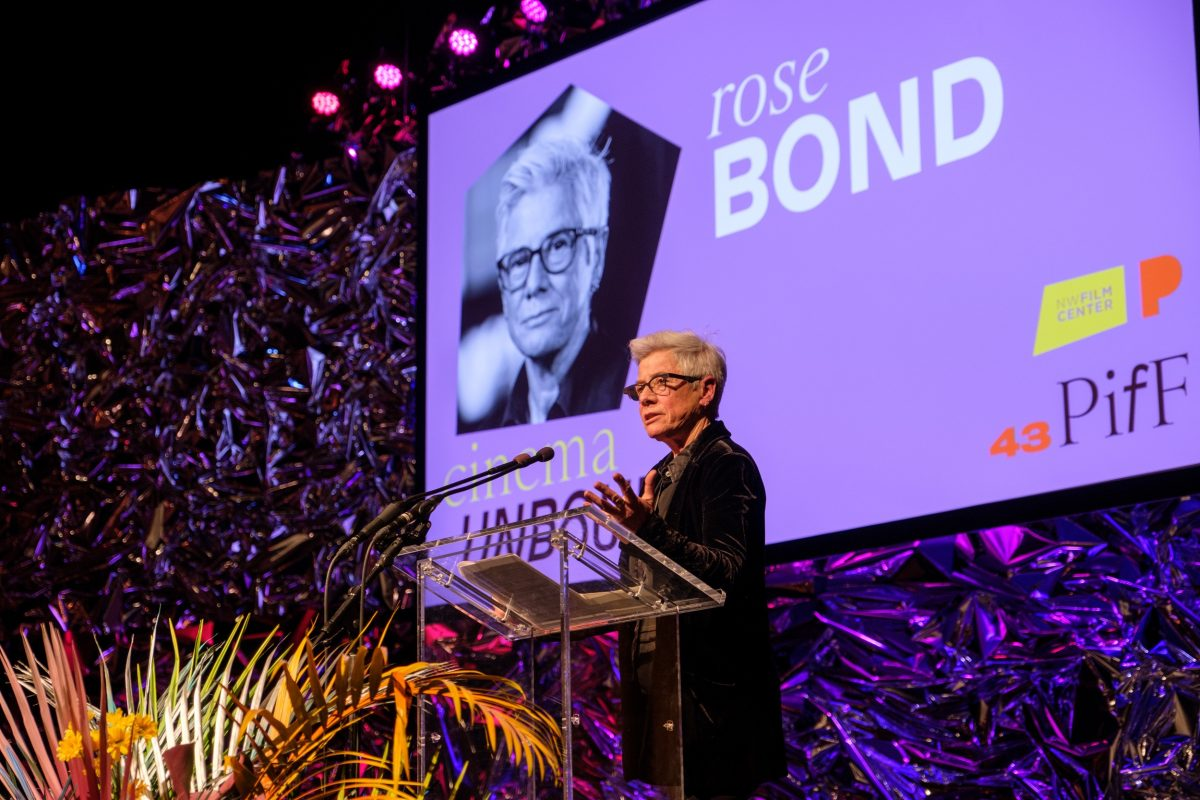 Photo of Rose Bond standing at a clear podium with a large screen in the background. Rose has short gray hair, wears black glasses, and is wearing a dark button up shirt and a large dark coat. Rose's left hand out outstretched toward the mic. A large fern grows in front of the podium. The purple screen behind has a photo of rose and reads rose BOND. cinema UNBOUND NW Film Center 43 PIfF.