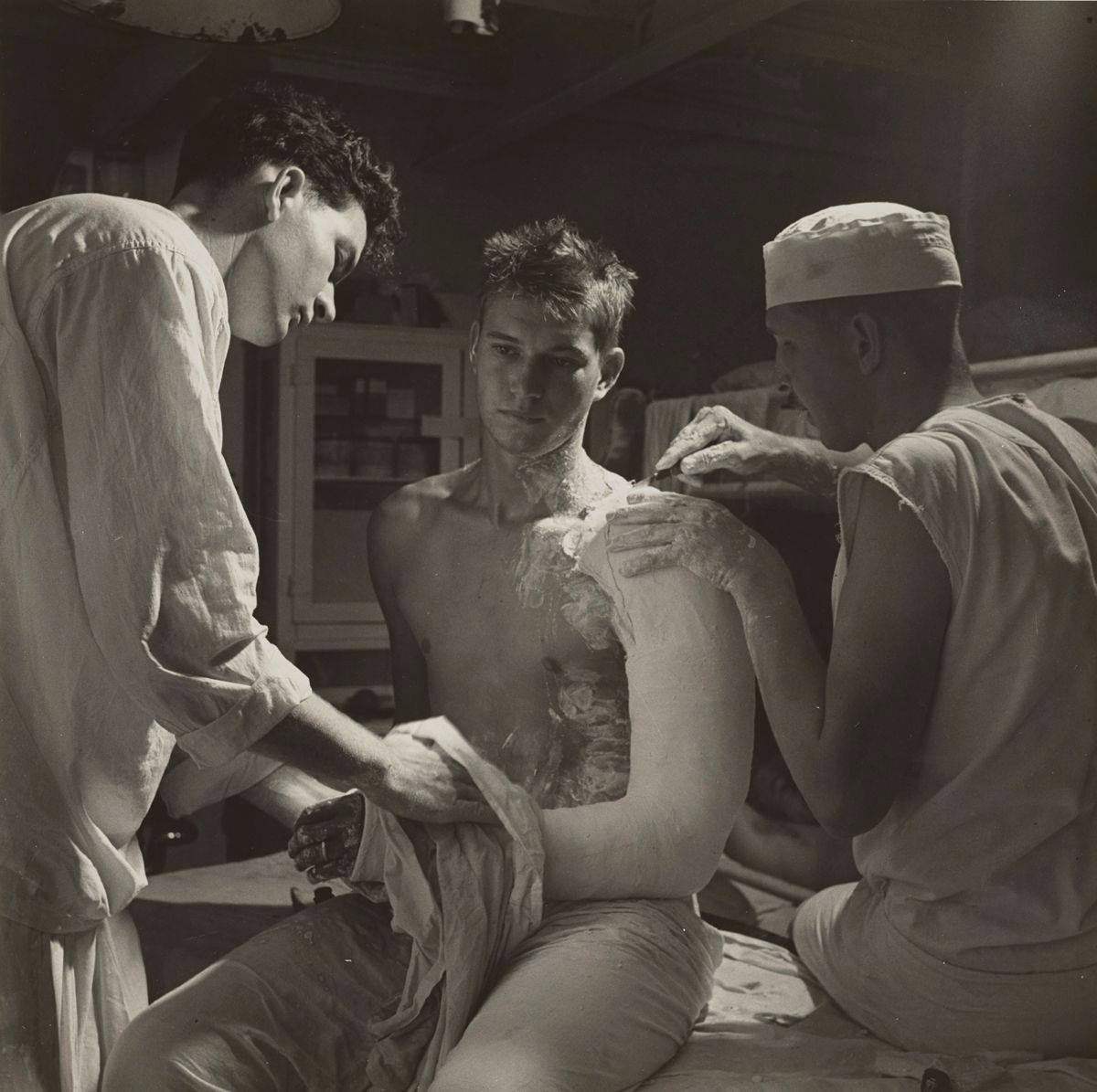 A black-and-white photograph of three light-skinned, young men. The central figure sits on a doctor's examination table, turned three quarters to the left while having plaster applied to his left arm. He stares off to the left, his hair spikey and messy, his facial expression somber. He is shirtless and having his arm, crooked at the elbow, set from shoulder to fingers in a plaster cast. Excess plaster is slathered and splattered on his neck, chest, and stomach. He wears a band on the ring finger of this left hand. At left, another young man is seen from the side, his head bent slightly forward, light from above cast on his face. He is using a cloth on the patient's arm. He has dark short hair, wears a loose-fitting shirt with the sleeves rolled up. At right, another young man is cutting away the rough edge of the plaster on the patient's shoulder. This man sits on the table with the patient, his back to us, the sleeves cut off his shirt, a small white cap on his head. The background shows a supply cabinet and bunks. Light streams down from the top right corner of the photo.