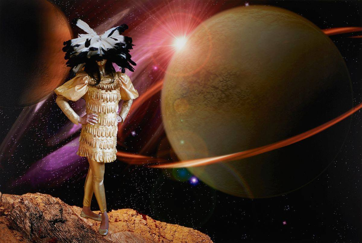 In this photo, a female figure stands at the left wearing an embellished gold tunic, leggings, and shoes, her hands on her hips, and a huge feather headdress that obscures the face. Her legs cross one in front of the other, toes pointing out in a dancer's pose. Gold jingles in conical shapes hang in horizontal rows for the full length of the textured tunic. Full, puffy sleeves end at the elbow, continuing to the wrist in a fitted fashion. The headpiece features black-tipped, white feathers splaying out from the crown, allowing some feathers to be viewed end to end. The top half of the face is covered by the feathers, the lower half and neck is coated in gold glitter. Long black hair extends from the head dress to below the shoulders. Gold, smooth leggings and gold ballet slippers complete the outfit. In the background, oversized planets fill the space. At right, an enormous muted grayish green, rough textured planet with a bright orange ring dominates the picture. A bright white object peeks out from behind the large planet at its top left, shooting rays of white light outward. A faint red-orange circle surrounds the light object, overlapping the huge planet's edge. At far left top, another planet, mostly in dark shadow fills the corner of the photo. Its color ranges from almost black in the shadow to rusty browns. Beyond the planets the sky is depicted in a deep inky black with a multitude of tiny white dots representing stars. The gold clad figure stands on a craggy stretch of rock that protrudes into the photo from the bottom left edge towards the center of the photo.