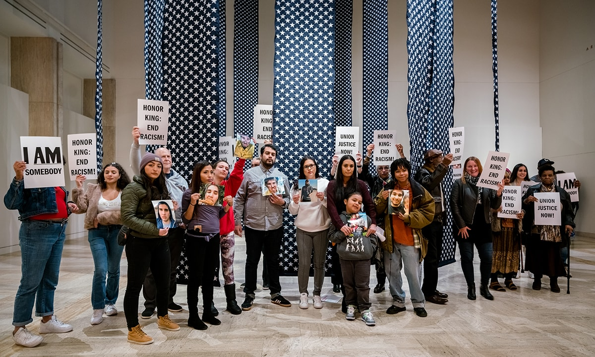 "20 people of varying ages, races, and genders stand in museum gallery holding signs that read I AM Somebody, Honor King: End Racism, and Union Justice Now! They stand in front of a Hank Willis Thomas installation titled ""14,719"" which is a series of 28 foot tall blue banners hanging from the ceiling covered in white embroidered stars representing gun deaths in the US in 2018."