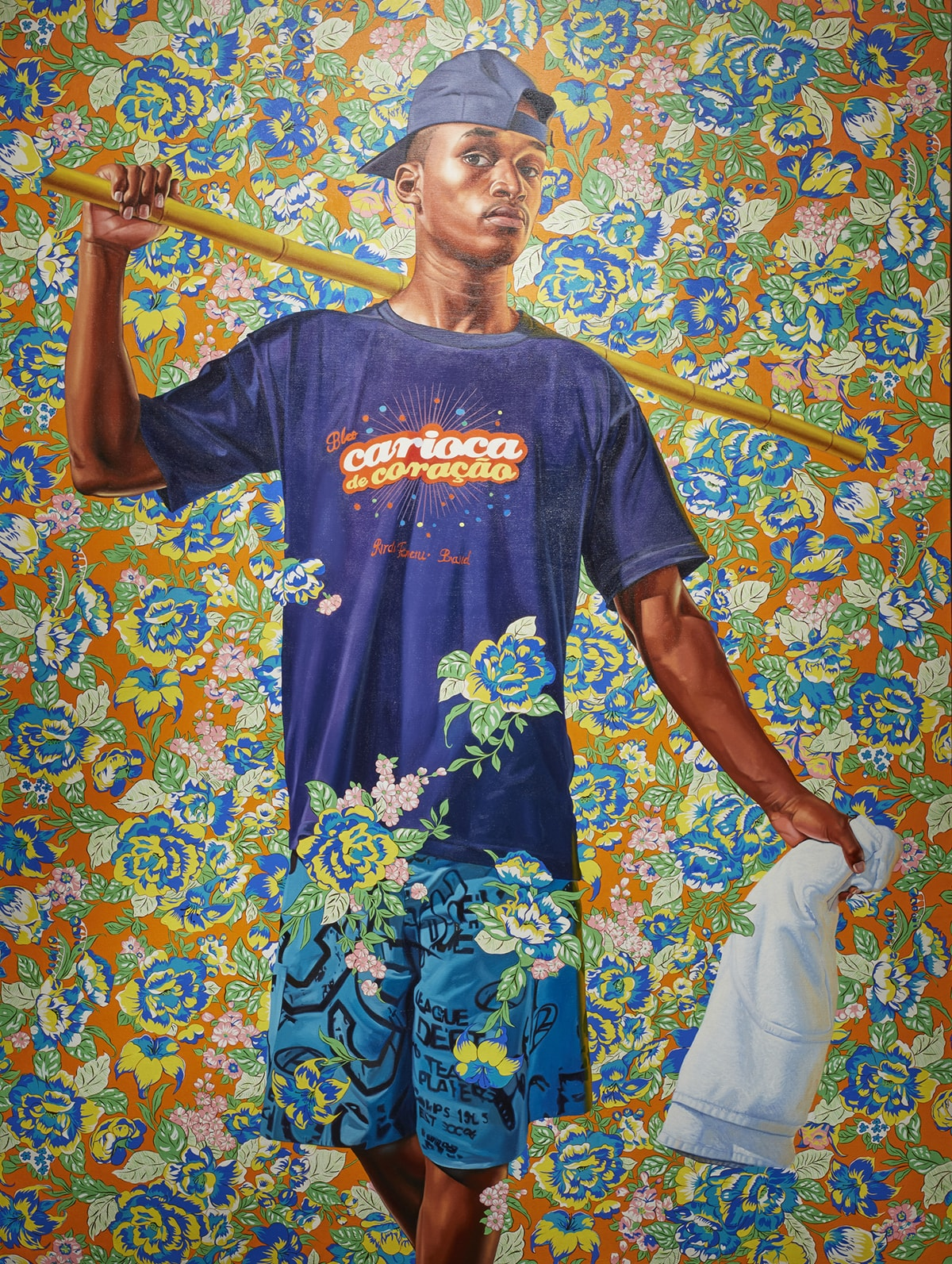 "An almost full-length portrait of a young, dark skinned man against a colorful, floral background. The figure is shown standing, facing the viewer or artist with the arm at left raised and bent at the elbow to create an L shape while holding a long stick of bamboo. The bamboo rests on the individual's neck and shoulder, passes behind his head and is seen extending to the right of the figure. The arm at right is held out from his side and in his hand is a white towel. The figure gazes directly out, head turned slightly to the right with a neutral expression. He wears a backwards blue ballcap and a blue t-shirt with the Portuguese phrase ""Bleo, carioca de coracao"". He wears knee length light blue shorts on which are printed phrases and large letters in black. The portrait ends at the figure's mid-calf. Surrounding him are large blue and yellow flowers with green leaves on an orange background. The overall effect is very busy. Some of the floral pattern is superimposed over the figure's shorts at the lower hem and hip area and the shirt at the mid-section."