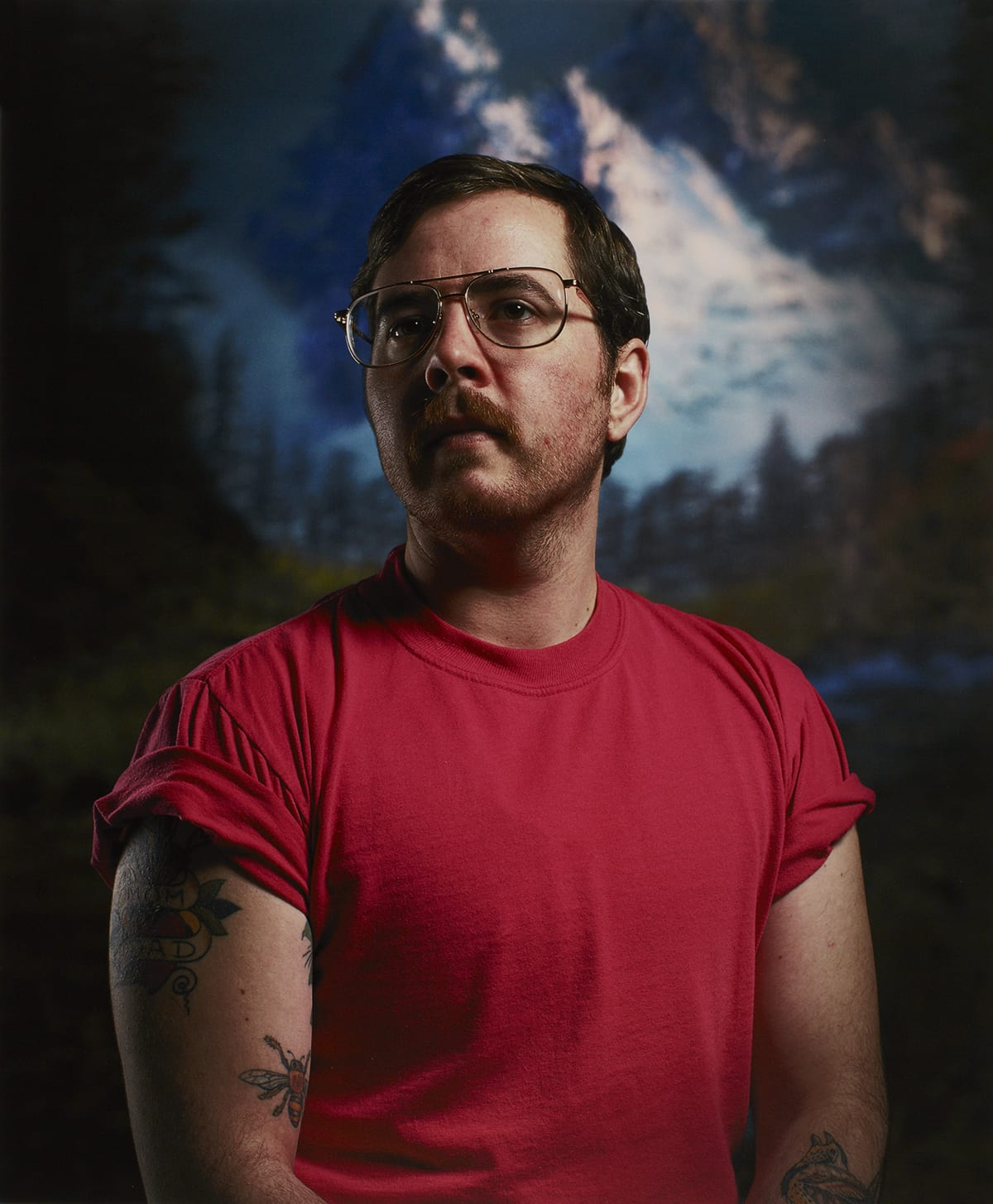 "A vertical rectangular portrait of a masculine-presenting individual shown from the midsection up. The figure is positioned to face the viewer or artist and their head is turned to the left. They have light skin, dark short hair, a mustache, and beard stubble. They wear metal aviator-style eyeglasses and a red short-sleeved t-shirt with the sleeves rolled up. The figure's bare arms show several tattoos. The upper arm at left has the words ""MOM"" and ""DAD"" within a heart design and another is of an insect. On the figure's forearm at right, part of a bird tattoo is visible. The background is slightly out of focus and depicts large, jagged, snow-covered mountain peaks in blues and whites. Below the mountains are pine trees and dark foliage."