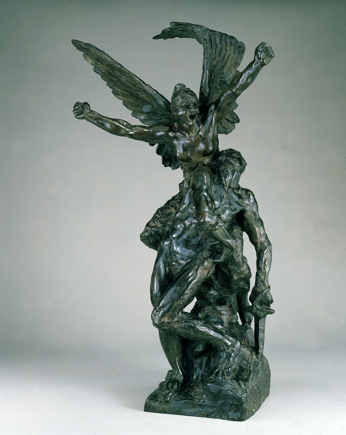 A photograph of a bronze sculpture showing two figures: the feminine presenting Spirit of Liberty and a masculine presenting combatant. The Liberty figure is positioned over the combatant. She is bare breasted with muscular arms raised in a V and fists tightly clenched. Her mouth is open wide as if shouting. She has a large pair of wings that rise behind her echoing the V of the arms. One wing is visibly broken and bent back on itself. The combatant is posed just beneath Liberty, and he looks up to her as if responding to her call. His nude body is set at a diagonal to Liberty's with his head thrown back to the right, and his torso, hips and legs crossing diagonally to the left of Liberty. The leg at right is bent at the knee creating another angle. The arm at left lies across his body with his hand resting at right. His other arm is extended downward and he holds a sword that is inserted in the rocky base. He uses the sword to support his weak body as he tries to rise up toward Liberty. The sculpture is highly varied in its textured, displaying muscles, feathers, smooth skin and rock. The bronze is dark, almost black in some places with brownish highlights.