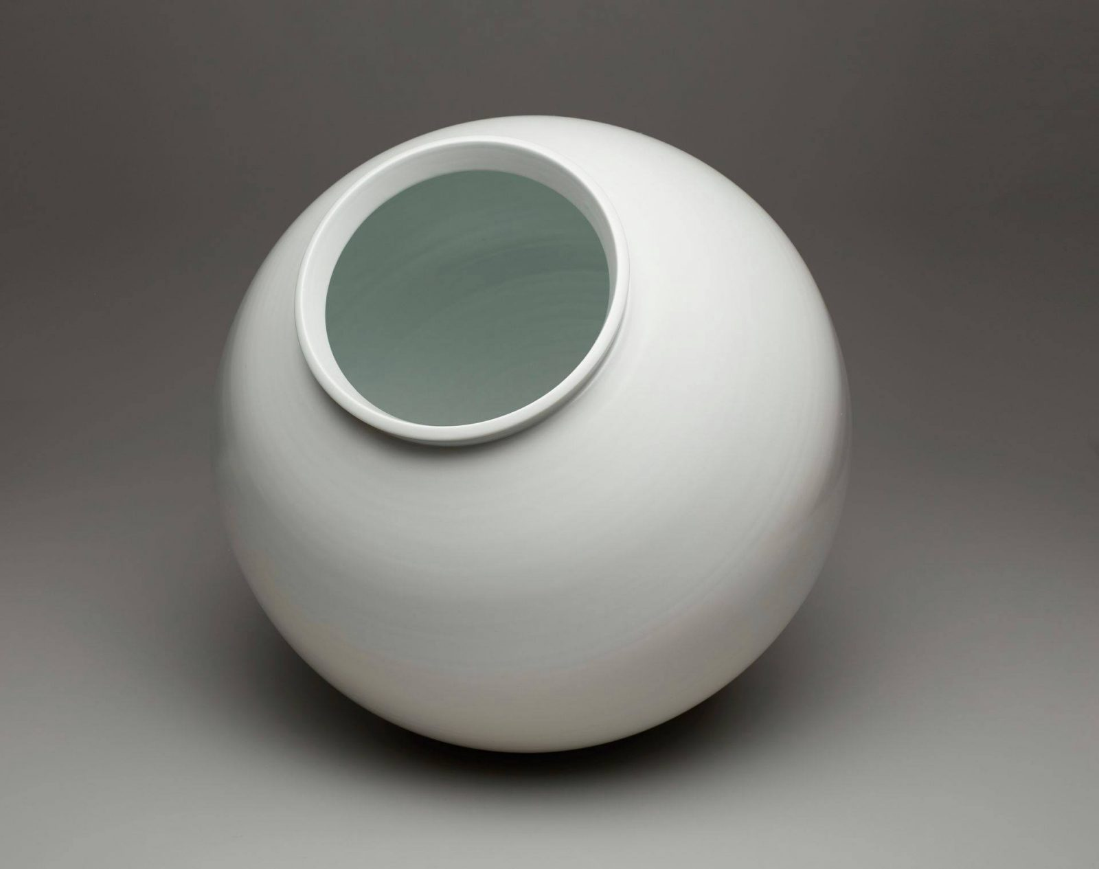 A photograph of soft-white, spherical-shaped jar that is subtly elongated vertically. It has a raised, upright lip that flares ever so slightly on a wide mouth. The base or foot is narrower than the mouth but mirrors its simple shape. Subtle striations run horizontally around the body of the jar giving the appearance of very faint texture. The jar is pictured against a gray background.