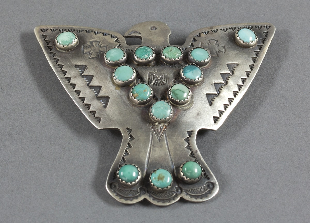 A photo of a silver bird shaped pin with wings open to each side. Its head and beak are shown in profile, facing left. The body of the bird is adorned with round turquoise stones set in an inverted triangle pattern. In the center is a small stamp of a thunderbird with its wings pointed down, head and beak facing right. Two small, stylized crosses are positioned on either side of the turquoise triangle. Just below this triangle is a small, stamped, inverted triangle with detailed decoration. There are single turquoise stones at the tip of each wing. The tail is depicted by three feathers with rounded tips and accented with three more turquoise stones in a row. Two vertical incised lines delineate the bird's tail feathers. Small, stamped, inverted triangles edge the wings and tail. Two rows of four larger inverted triangles appear on the wings parallel to edging stamps. The stamped detail is a darker shade of silver color than the rest of the metal. The turquoise stones vary in color from pale blue to blue-green and have different veining and patterns including deep blue, white, brown, and green.
