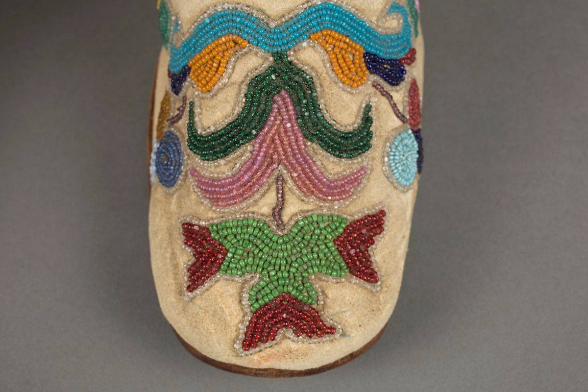 A pair of colorfully beaded, low-heeled ankle-high boot style shoes, pointing towards the right, seen in a three-quarter view against a gray background. Beige leather with beaded floral decoration on the toe box and both inner and outer sides of the shoes depicting leaves, flowers and abstract shapes in shades of blues, dark and light greens, burgundy, lilac and yellow almost cover the shoes. Beige laces thread through metal eyelets at front, the bright yellow lining is visible the length of the throat of the shoes. A seam is across the instep, they have brown soles and wooden, stacked heel. The toes of the shoes lift slightly from the smooth surface on which they are resting.