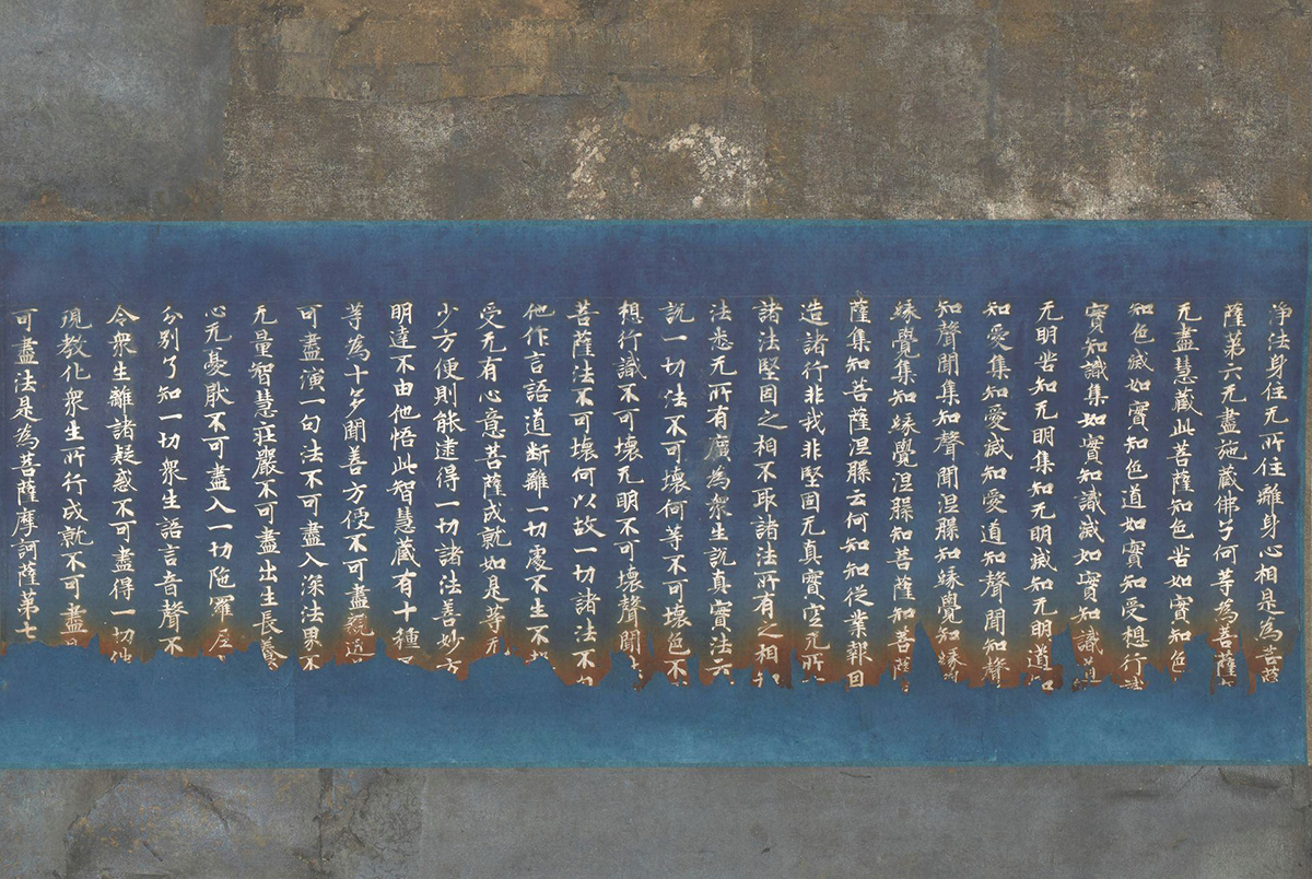 Rectangular detail of the central section of the scroll showing a wide, deep blue or indigo band running from side to side containing 28 rows of calligraphy characters in silver ink. The inked characters line up uniformly along the top of the rows but at the bottom the characters become jagged and uneven and the deep blue turns to a rusty brown. Two bands of mottled bluish-gray, taupe and cream metallic foil run horizontally along the top and bottom of the calligraphy.