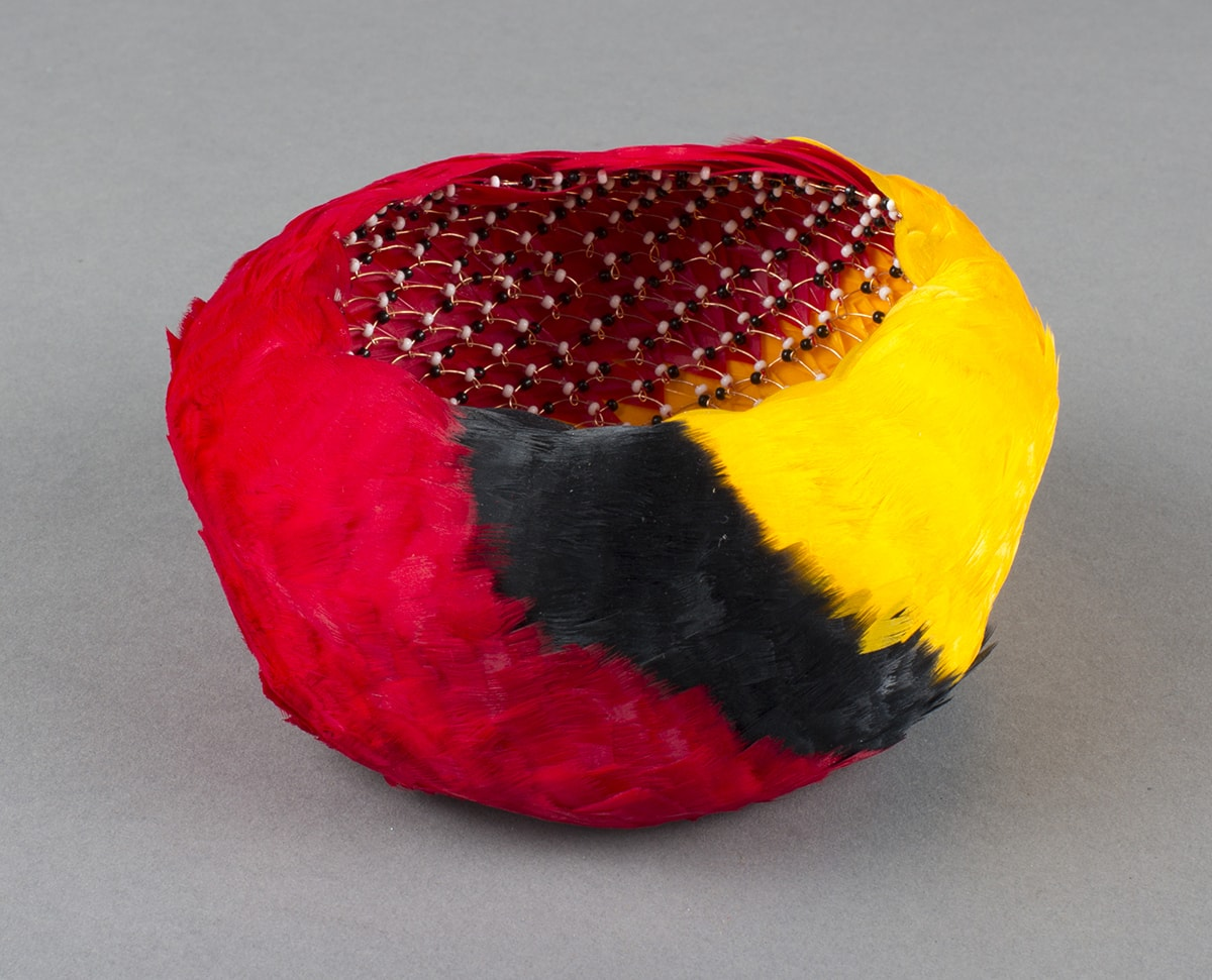 'ahu 'ula, Bernice Akamine, size 2 1/2x 5 inches in diameter, dyed goose feathers, copper wire, and glass seed beads. A small, feather-clad, bowl-shaped basket shown from slightly above to provide a view inside. The outside of the basket is covered in overlapping feathers that create dense swaths of bright colors. From left to right, the colors are red, black, and yellow. The colors appear to swirl around the basket on a diagonal with each color of feather blending slightly into the next. Inside, the basket's structure is revealed to be composed of a series of looped copper wires adorned with alternating small black and white beads. The feathers are clearly visible though the loose weave of the basket's structure.