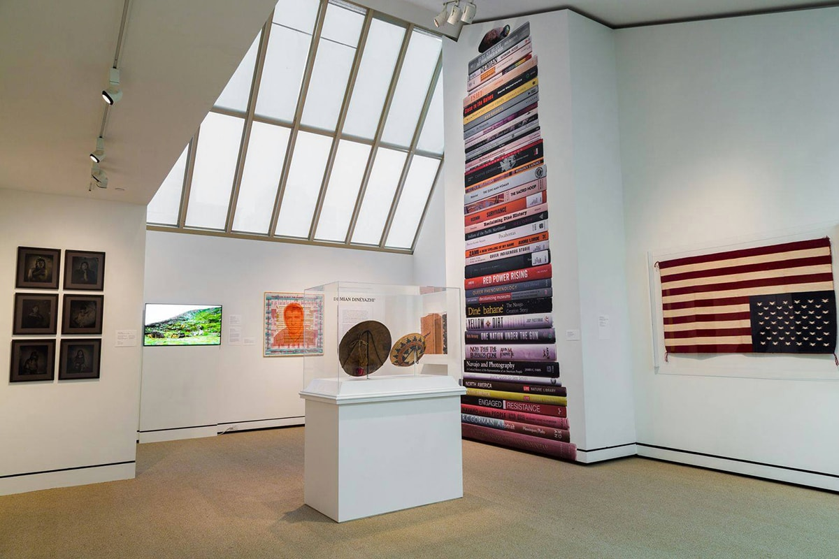 """A photograph of a gallery interior featuring works of art and a large skylight window. The skylight window is at center top and extends halfway down the photo. The room has angled ceilings and walls that jut out into the room. On the wall space to the right of the skylight is an image of a stack of books that reaches from floor to the top of the double height ceiling. Some titles are: Bury My Heart at Wounded Knee, Red Power Rising. The Sacred Hoop, One Nation Under the Sun, Survivance and Yellow Dirt. To the far right and hanging on the wall is Bertha Harvey's """"Flag Rug.' This woven, wool depiction of the American flag is hung upside down with the stars at bottom. In the center of the room is a free-standing pedestal with an acrylic enclosure containing a Native American basket and another artwork shown from the back. Behind the pedestal and below the skylight there is a video monitor showing a green landscape and a square portrait surrounded by text. The artist's name, Demian DinéYazhi', is on the wall above a large wall label. At far left, six black-and-white portraits hang in three rows of two each. The gallery walls are white and the carpet is beige."""