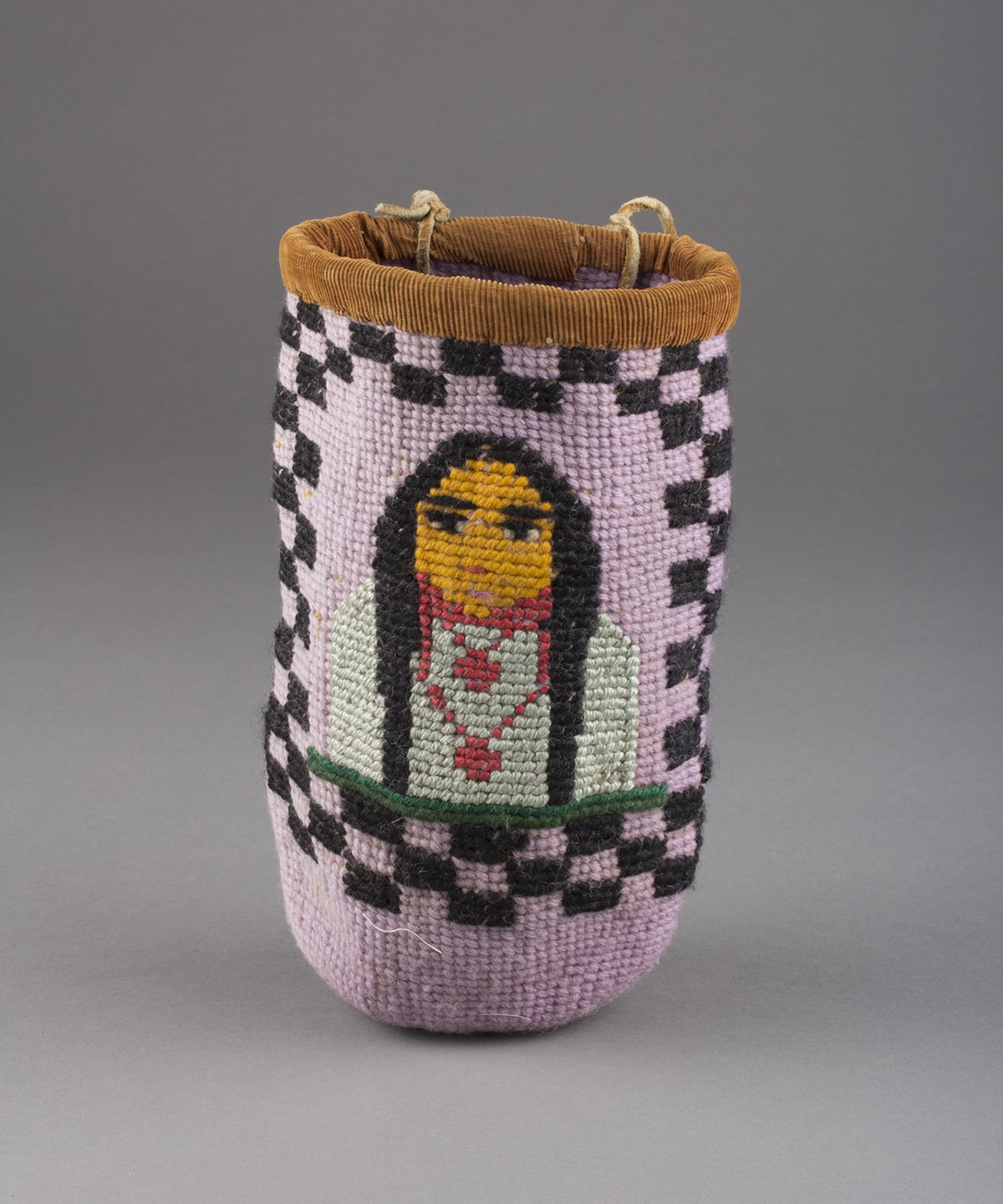 Berry bag, Umatilla artist, commercial dyes, buckskin and cotton, size: 10 x 5 ¼ inches in diameter. A tall, cylindrical, woven basket with the image of a portrait surrounded by a black checkerboard pattern. The figure is positioned at the center of the basket, showing the head and upper body. The individual has long black hair, black eyes and brows, and a golden yellow face. Two rose-colored necklaces adorn an off-white shirt. A dark green bar runs along the bottom of the figure. The body of the basket is lilac and the black checkerboard pattern surrounds the figure with two rows of check at top and sides and three rows at bottom. The rim of the basket is covered in a brown corduroy fabric. Two buckskin ties are seen knotted at the back of the rim.