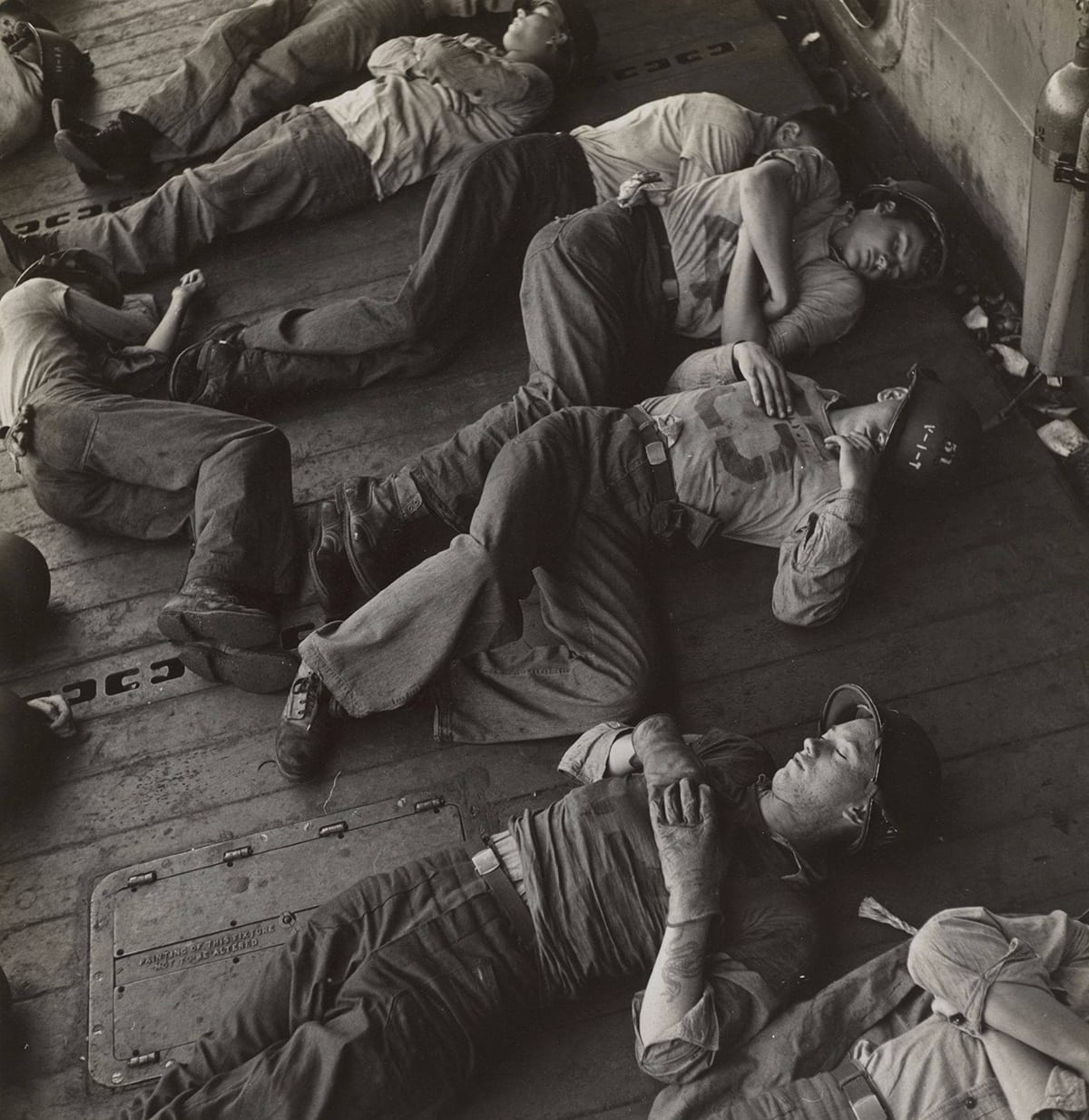 Victor Jorgenson, Untitled (relieved of their long ordeal and still in battle helmets, the exhausted crew sleeps) size: 10.5x10.5 inches, gelatin silver print. A square, black-and-white photograph of six young male soldiers lying asleep on the deck of a ship. The soldiers are viewed from above and are positioned diagonally across the photo with their heads towards the top right and feet towards the bottom left. At far left, one soldier lies on his side near the other soldier's feet. He is positioned vertically in the photo with his head near top left. They lay on their sides with their knees drawn up or on their backs and are fully clothed in khakis, boots, and sometimes helmets. The decking beneath them runs diagonally and parallel to the men. The photo captures portions of other soldiers also sleeping suggesting a crowded deck of sleeping men.