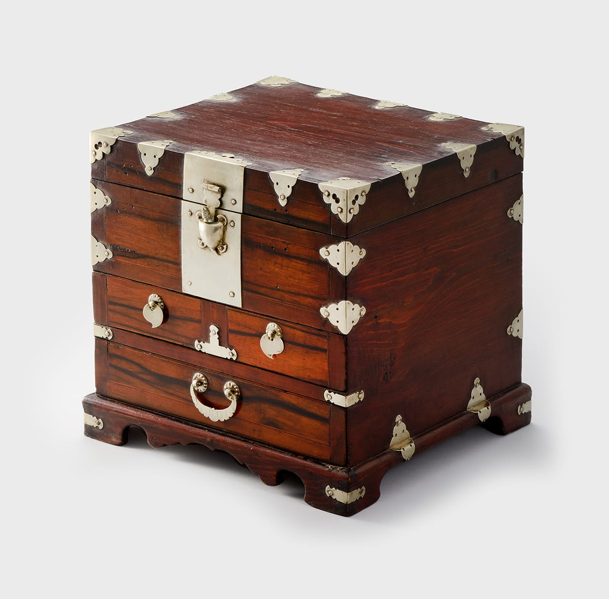 Comb Chest, 11 1/8 in x 10 1/2 in x 11 5/8 inches, persimmon wood with white brass (baekdong) fittings. A photo of a wooden, cube-shaped chest with numerous brass fittings decorating its edges. The chest is a warm brown with dark graining. On the front of the chest, near the top, is a latch in the shape of a turtle on a large smooth plate. The top of the latch is in the shape of the turtle's head and is attached to the lid by a horizontal hinge. Below the plate, there are two, small drawers adjacent to each other, each with a flat, round pull with a small tail at the bottom pointing toward the outside edge of the chest. Below these drawers is a long drawer with a pull in the shape of a stylized bat, its wings outstretched. The edges of the chest are embellished with triangular fittings that have scalloped edges and tiny, pierced holes. The fittings sit over the corners and edges of the chest at right angles. The chest sits on raised feet connected by a decorative apron.