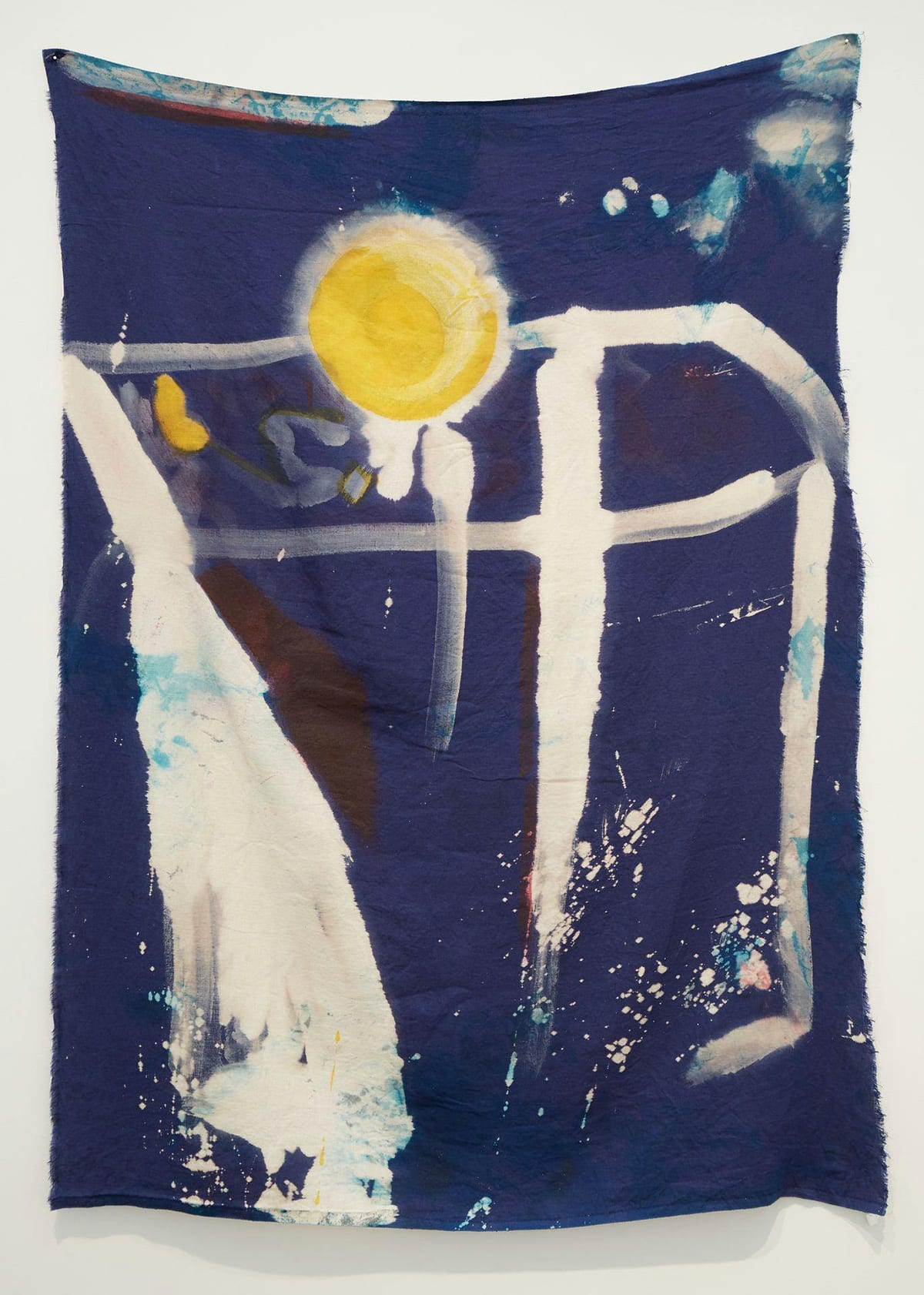 W.L.L.B.L.N.D.N.E.S., Kristan Kennedy, 50 x 42 inches, ink, dye, bleach on linen. A photo of a vertical rectangular length of cloth hung from the upper corners with the rest left to hang freely. The mostly indigo cloth has a round bright yellow circle near the top at center. The circle shows uneven color with a crescent shape suggesting removed color on its right side. Around the circle, a halo of white bleaching radiates outward from the yellow sphere. Larger areas of white drip from the bottom of the sphere. To the left is a short, thick blob of the same bright yellow. A horizontal bleached line runs behind the circle from left to right angling downward at far right. Just to the right of the sphere two thick bleached lines run vertically ending a third from the bottom in splatters. They are bisected by another horizontal line under the sphere. At left starting at the two horizontal lines, a thick bleached area travels downward widening into a wedge shape and continues to the very bottom of the fabric. It is unevenly bleached with some indigo showing through. White splatter marks decorate the bottom third of the cloth. At the upper right corner of the work, splotches of white are overlaid with a lighter blue color. The fabric is wrinkled and worn with frayed edges and loose threads. The borders of the cloth are uneven.