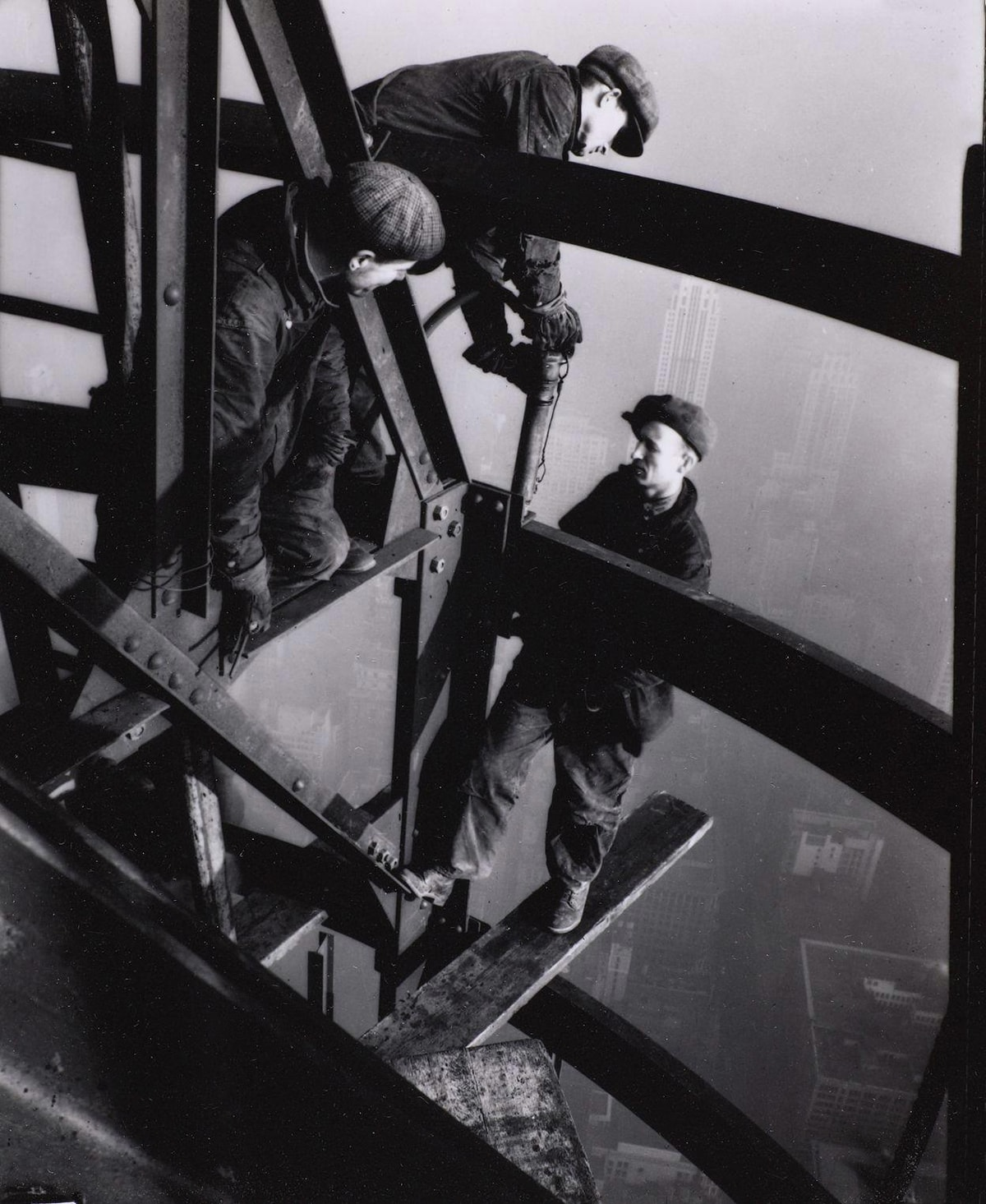 Lewis W. Hine, Top of the Mooring Mast, Empire State Building, 4 7/8 × 3 ¾ inches, gelatin silver print. A vertical rectangular, black and white photo of three light skinned men working on steel girders above a hazy cityscape. Three wide girders run parallel and diagonally from the upper left to the lower right. Other beams form a triangular structure near the upper center. One man kneels in this triangle while watching another to the right as he leans over appearing to rivet a beam below. The third man is standing at center right on a wooden plank that balances on a lower beam and juts out into the open air. The men wear work clothes of coveralls, boots, and flat caps. They do not wear safety gear. City buildings can be just made out through the haze behind them.
