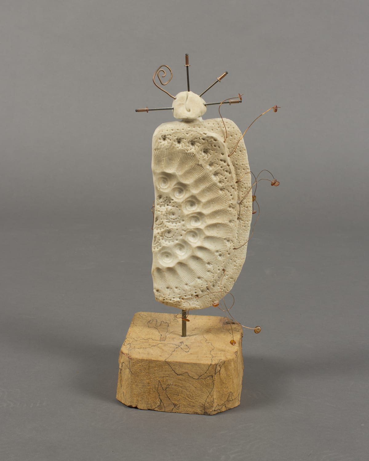Dancing in the Wind, Lillian Pitt, 14 ¾ x 5 7/8 x 4 7/8 inches, clay, beads, wood, and wire. A photo of a sculpture composed of three main parts: a body, a base, and a finial. The pale-beige clay body is shaped like a vertical rectangle with rounded corners and is highly textured with imprinted patterns. The bottom right corner is rounded off further than the other corners. The imprinted patterns appear to have been made with shells and form concentric semicircles similar to how the bands of a rainbow are arranged. A row each of scallop and nautilus shell imprints form arcs on their sides starting at the top and ending at the bottom. The balance of the body is dotted with the indentations of shell markings overall. Protruding irregularly from the right side of the body are bent copper wires with amber colored beads at the ends. Each wire is bent differently. The body is attached to a thick, chunky wood base by a short, metal rod. The blond wood of the base is traversed with thin dark lines that seem to outline the grain. At top, the finial is connected to the body by clay and is an irregular spherical shape with metal rods radiating out at 9, 12, 2, and 3 o'clock. At 10 o'clock, a copper wire curves into a spiral.