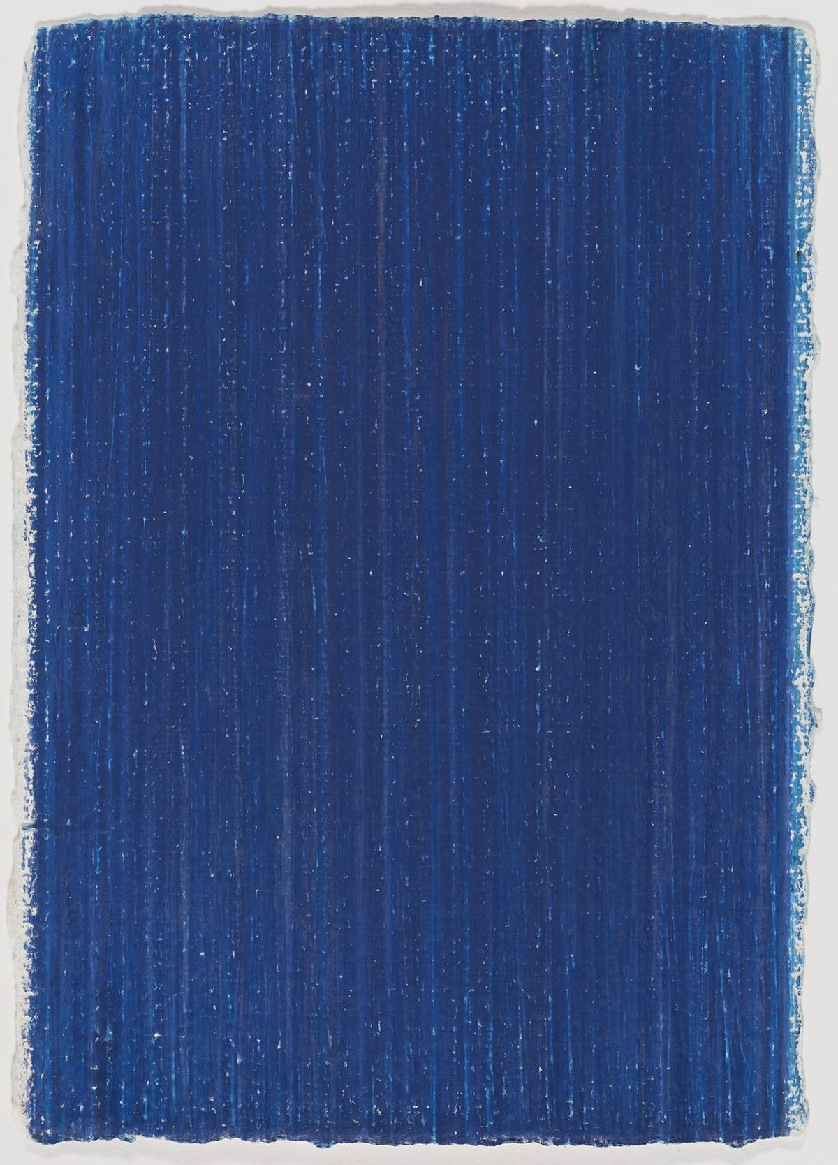 Prussian Blue, Vincent Hamel, 11 7/8 x 8 ½ inches, wax crayon on handmade paper. A vertical rectangular work composed entirely of a field of deep blue. Vertical lines create texture in the shape of variegated shades of deep blues with flecks and streaks of white throughout. The edges of the work are uneven and the nature of the crayon work reveals itself in scratchy, jagged borders