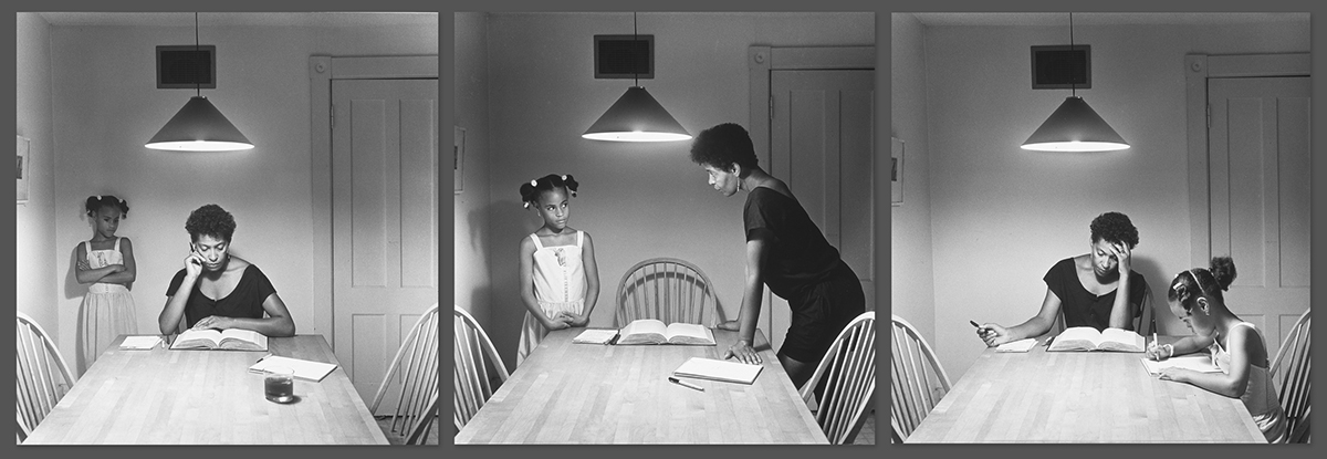 Untitled (Woman with daughter) from the series Kitchen Table, Carrie Mae Weems, each image 27 ¼ x 27 ¼ inches, gelatin silver prints. A series of three black-and-white photographs, positioned side by side, featuring a young Black girl and a Black woman in a room at a large table. The first photo shows the woman with short, dark hair and a dark dress seated at the end of a long, wooden table under a triangular overhead light. She looks down at an open book with her hand at left resting on her cheek and her arm at right resting on the thick book. Beside her to the left sit a notepad and pens. On the right side of the table is a notebook, pen, and a glass of dark liquid. To the left and behind the woman, stands a young girl in a light dress with shoulder straps, her hair up in pigtails. She stands with her arms folded and looks towards the book on the table. At right is a closed door and there are two chairs on either side of the table. The second photo shows the same setting with the woman now standing on the right side of the table leaning forward with her hands on the table. She looks directly at the girl now standing at left with hands clasped and resting on the table. The two stare intensely at each other. The third photo shows the woman back in her seat at the end of the table, left hand on her forehead, a pen in her other hand while she looks down at her book. The child is now seated at the right side of the table and is drawing in the notebook.