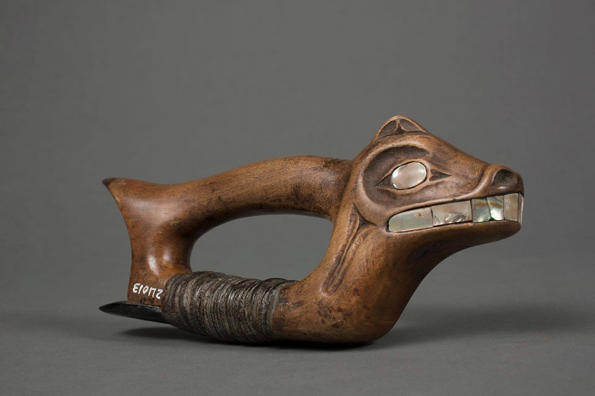 Adze, Haida artist, 4 x 9 ½ x 1 5/8 inches, wood and steatite with abalone shell inlay. A photo of a wooden adze with the head of an animal containing abalone shell facial features. The animal head is at the right side of the woodworking tool and has a small upright ear, large shell eyes, flared nostrils, and a wide mouth showing large shell teeth. The wood is a warm brown and very smooth all over. The abalone shell is a grayish silver with flashes of bright white and deeper tones of gray and brown. Extending from the back of the head to the left is the tool's cylindrical handle that ends in a point like a short tail. The animal's neck extends down to the base of the tool with the handle and base connecting at each end and forming a void and room for the artisan's hand. The base is wrapped with thin strips of dark brown leather that have compacted with use. These leather strips hold a piece of a steatite to the base. The steatite extends back past the end of the adze. Old museum accession numbers are seen at the bottom rear of the base having been added years later.