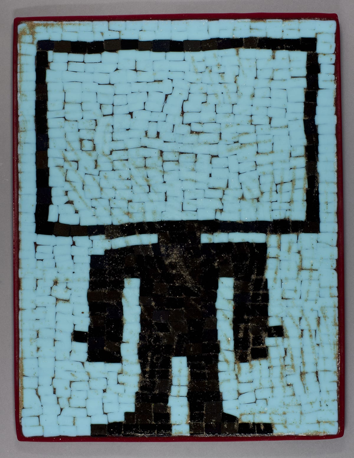 Flat Screen, Joe Feddersen, 19 ½ x 25, fused glass. A photo of a vertical, rectangular glass panel showing a simplified humanoid figure with an oversized rectangle for a head. The panel consists of a multitude of small glass rectangles that have been fused together forming the figure in black outline against a brick-like background pattern. The figure's head is the outline of a large, horizontal rectangle resembling a flat screen TV. The neck, shoulders, arms, hands with thumbs sticking out, a torso, two legs and feet complete the figure. The figure is set against light blue glass rectangles that are stacked to form uneven rows with space between them being black. The piece is edged with a thin, red border.