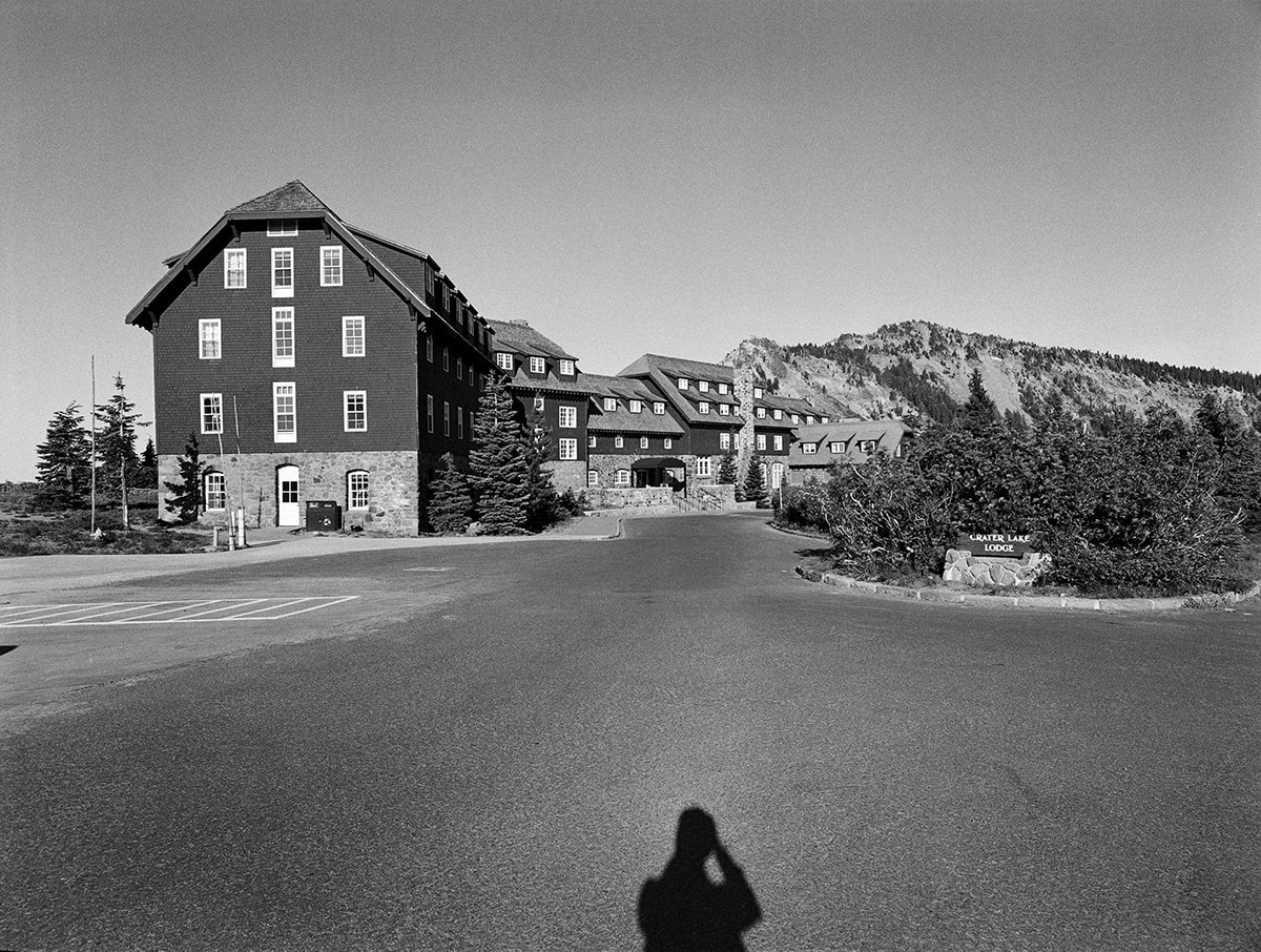 "Crater Lake Lodge, Jonathan Calm, pigment print. A horizontal rectangular, black-and-white photo of the Crater Lake Lodge buildings and its driveway entrance. The top half of the photo features the lodge seen from one end and running diagonally back and across the photo's middle ground. The buildings that compose the lodge are faced in light-colored stonework from the ground to just above door height with dark cladding finishing the rest of the structures. Rows of white-paned windows dot the attached buildings that are of varying heights. To the left of the lodge is a rocky hilltop with sparse vegetation and to the right are several evergreen trees. The bottom half of the photo shows the expansive blacktop driveway that extends out from the lodge entrance and to each side. At bottom center is the photographer's shadow, shown from chest up. At center far right, shrubbery backs a wooden sign mounted on a stone platform. The sign reads: ""Crater Lake Lodge""."