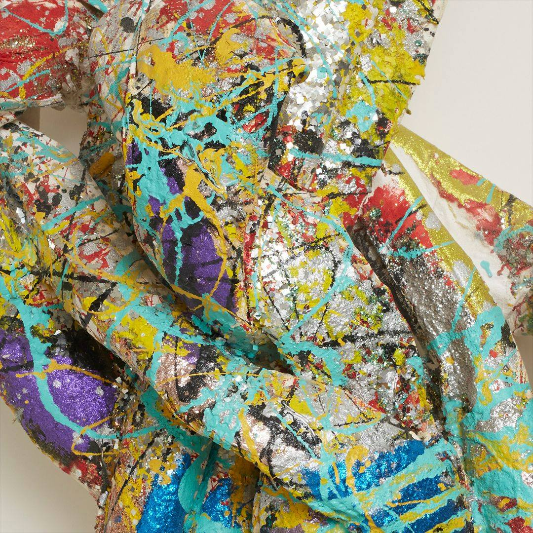 A closeup photo of the sculpture showing the structure of the knot and splatter work. Bright colors and glitter cover the thick strands that compose the sculpture.