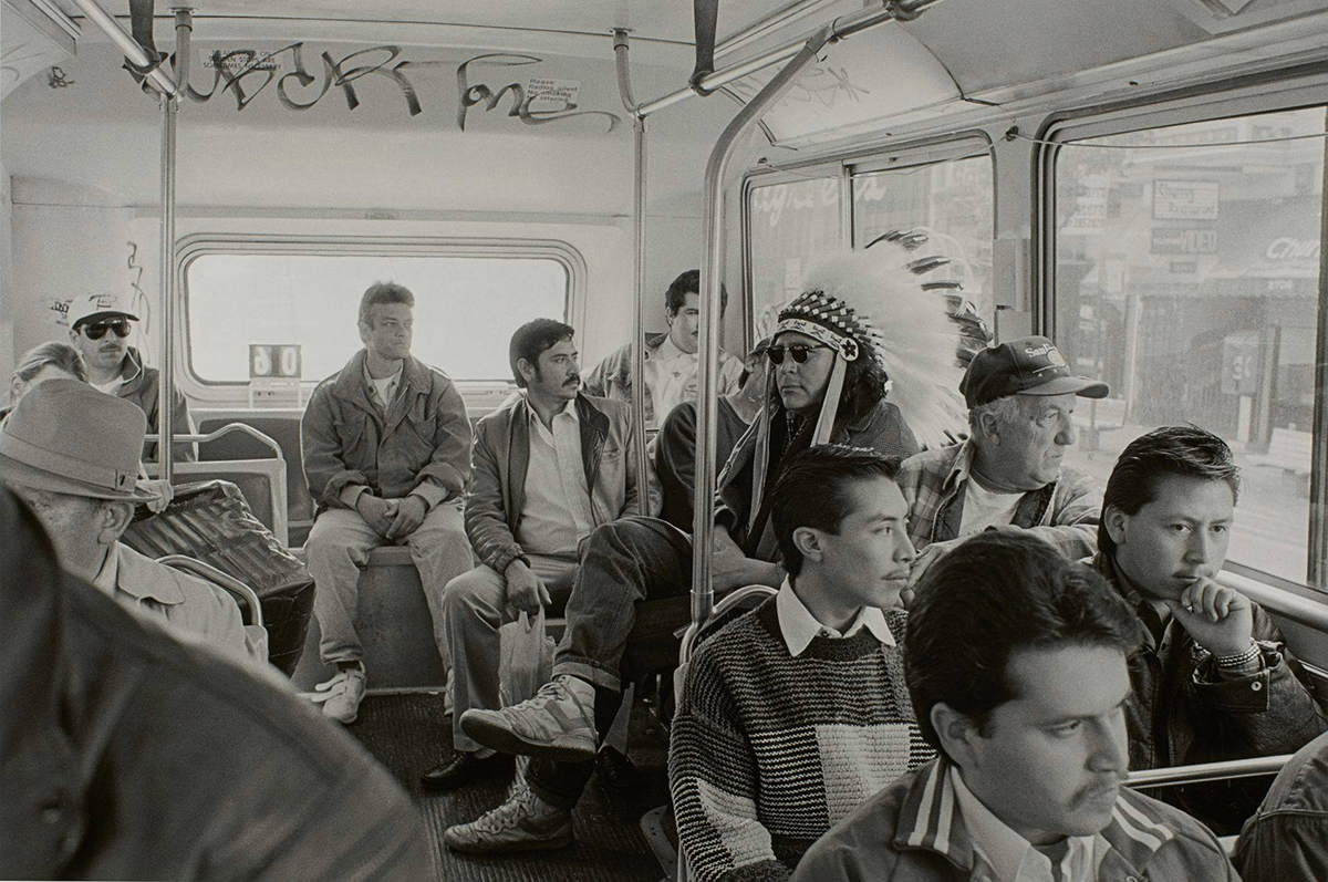 Indian Man on the Bus, from the series Indian Man in San Francisco, 16 x 20 inches, gelatin silver print. A horizontal, rectangular, black and white photo of the crowded interior of a bus featuring a man wearing a Native American feather headdress. The view is of the last few rows of the back of the bus showing a group of seated male presenting individuals. At right, a man is seen wearing a large Native American feather headdress composed of dark tipped, white feathers that radiate from a beaded band across the top of the man's forehead. He wears a neutral expression, dark sunglasses, a jacket, cuffed jeans and high-top sneakers. He is sitting on one of the inward facing bus benches and so faces towards the left. The other figures around him sit in rows: three behind the man in the headdress, across the back wall of the bus, four seated in rows in front of the man and several partially visible figures to the left of the photo. The men, all of whom look past the man in the headdress or out the window, appear to be of varying backgrounds such as White, Hispanic or Asian. A city street scene is visible through large bus windows at right.