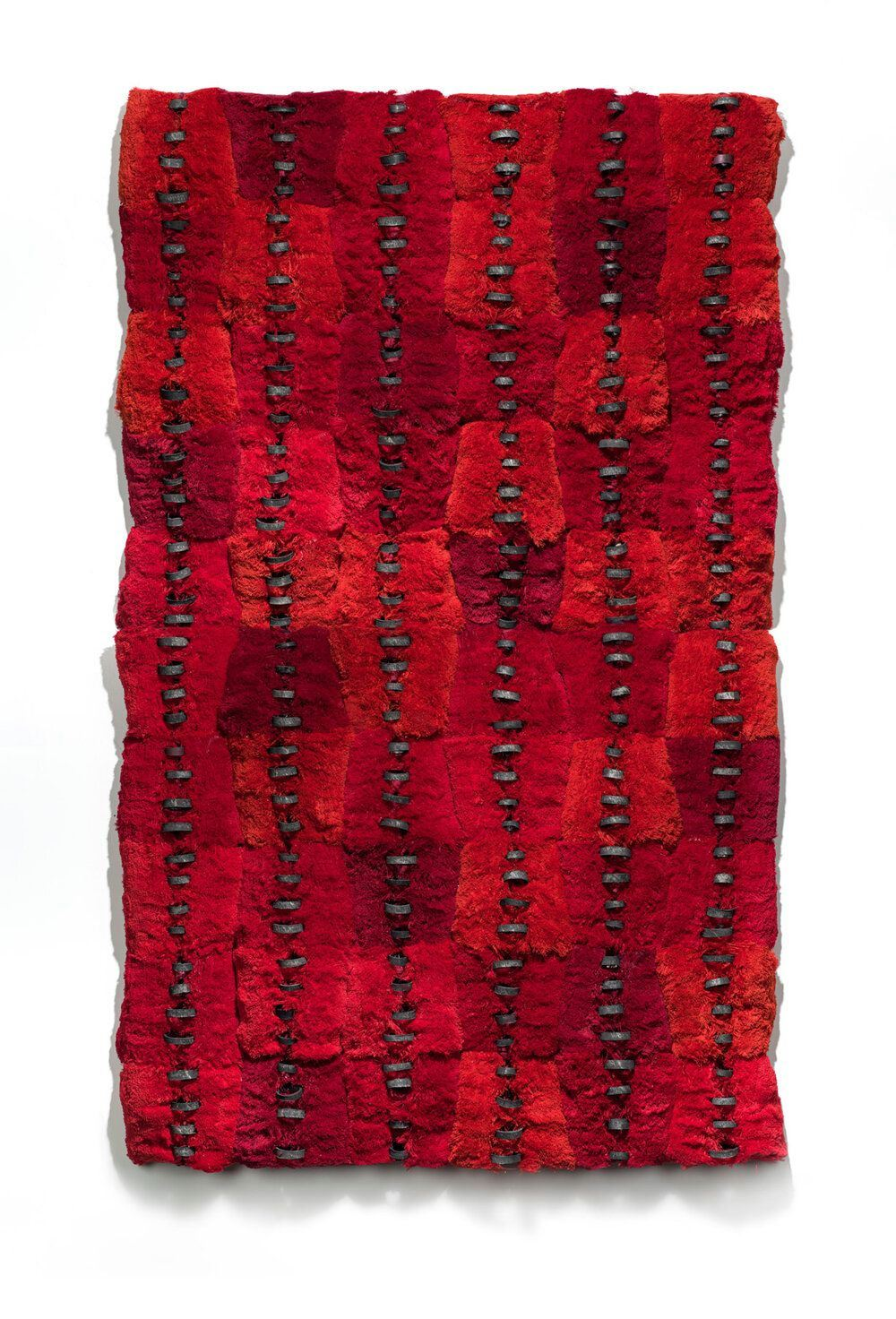 "Proximate Parcels, Brenda Mallory, 70 x 34 x 4 inches, deconstructed thread spools and cores. A work composed of interlocking trapezoid shapes fitted together to form a vertical rectangle with six vertical rows of dark charcoal colored ""stitching"" running lengthwise. The trapezoid shapes are made up of red fibers, appear fluffy and vary in shades of deep red to tomato red. The edges of the work are uneven and undulate slightly with the shape of the trapezoids. The stitches embellish the trapezoid shapes but do not actually join them together."