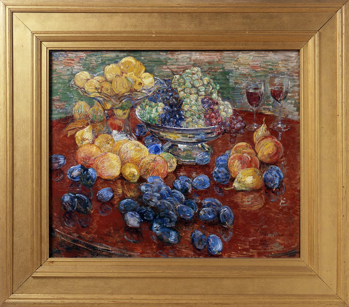Childe Hassam. Oregon Still Life, 25 x 30 ¼ inches, oil on canvas. A painting of an assortment of fruit laid out on a round, dark brown table, the edges of which are mostly out of frame. At top, at 11 and 12 o'clock, are a glass bowl with a tall stand brimming with yellow apples that sits beside a squat, silver bowl holding green, purple, and red grapes. Just below the glass bowl are more yellow apples, some with a hint of pink. Further down the painting and scattered over the table are deep blueish-purple plums. At three o'clock are a grouping of a half dozen peaches and pears set near two half-filled glasses that suggest wine. The painting technique is bold and uses dry brush strokes. Paint is heavily layered, revealing the colors underneath in areas. The table and fruit are set against a background heavily painted with horizontal strokes in muted greens, terra cotta, and whites with deep yellow.