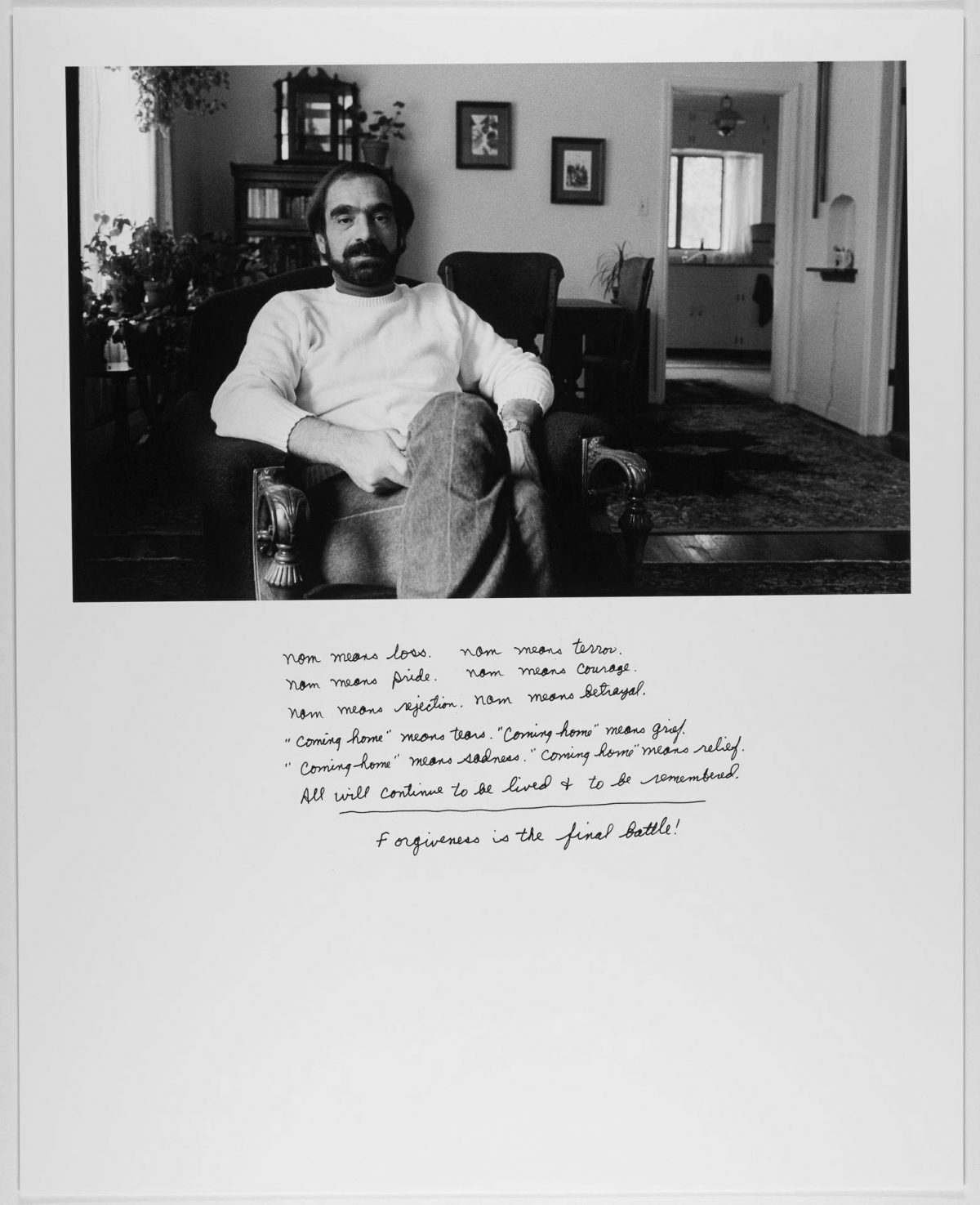 """From the portfolio War Story: Vietnam Veterans, Don Unrau, 13 5/16 x 14 1/8 inches, pigment print. A horizontal, rectangular, black and white photo positioned on the top half of a vertical white rectangle. The photo shows a white man sitting in an armchair, facing the viewer with legs crossed at the knee. He looks directly at the viewer with a neutral expression. He has dark hair and full beard, wears a white shirt and jeans. Behind him is the interior of a home with plants, dining room table and chairs and a kitchen seen through a doorway. Below the photo is a poem in the man's own handwriting. It reads: Nam means loss. Nam means terror. /Nam means pride. Nam means courage. / Nam means rejection. Nam means betrayal. / """"Coming home"""" means tears. """"Coming home"""" means grief. / """"Coming home"""" means sadness. """"Coming home"""" means relief. / All will continue to be lived & to be remembered. / Forgiveness is the final battle!"""