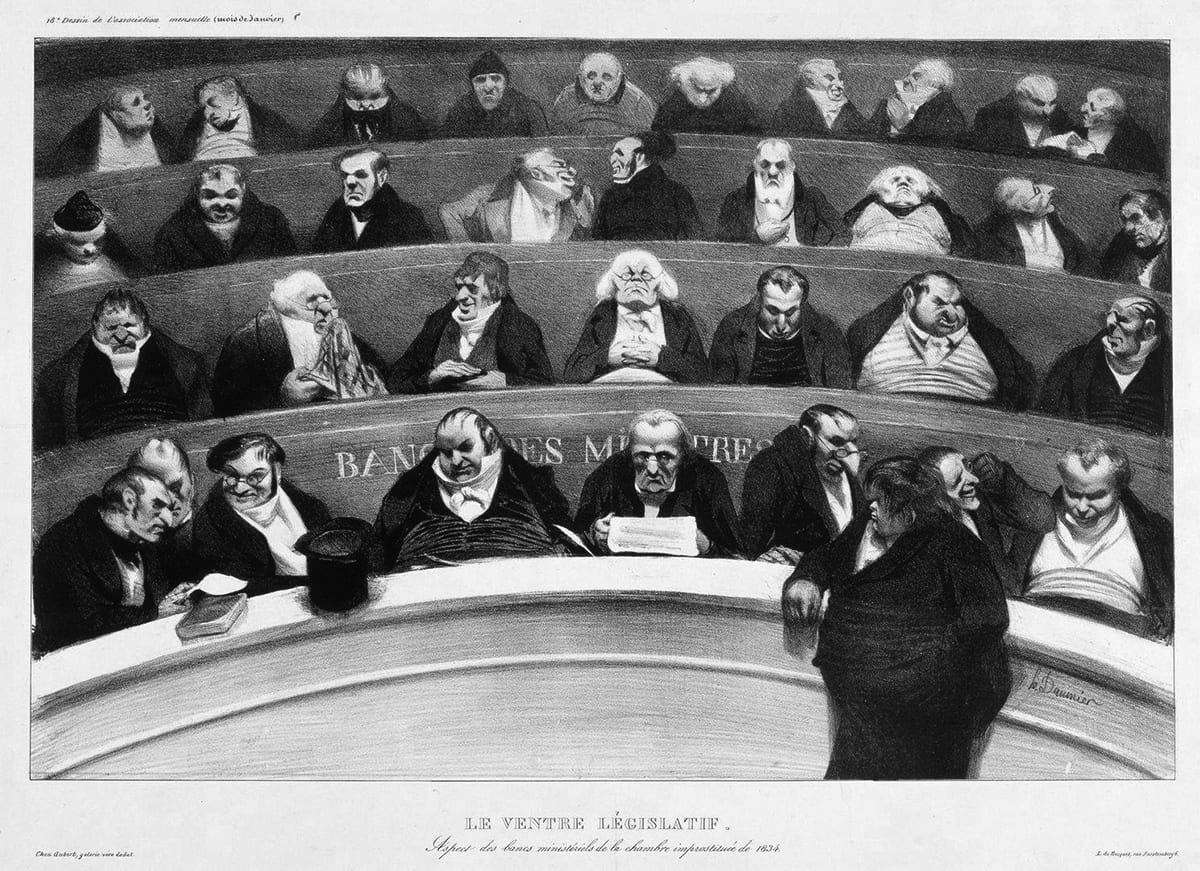 Le Ventre législatif: Aspect des bancs ministériels de la chambre inprostituée de 1834 (The Legislative Belly: Aspects of the Prostituted Ministerial Benches of 1834), Honoré Daumier, 11 1/8 in x 17 1/8 inches, Lithograph on wove paper. A horizontal, rectangular black and white print showing rows of men sitting in curved, tiered seating. The four rows are stacked one upon another showing how each row is higher than the one below it. Each row is packed with between seven to ten older men, most having narrow shoulders and broad middles, dressed in dark coats and the high white collars of the time. The waist high railing allows only their upper bodies to be visible. Some confer with heads together or are turned to speak to each other, some appear to be dozing. At lower right, one large man dressed in black with shaggy hair stands in front of the bottom railing turned to the left, his arm resting on the railing. At left, a top hat and a book also rest on the railing.