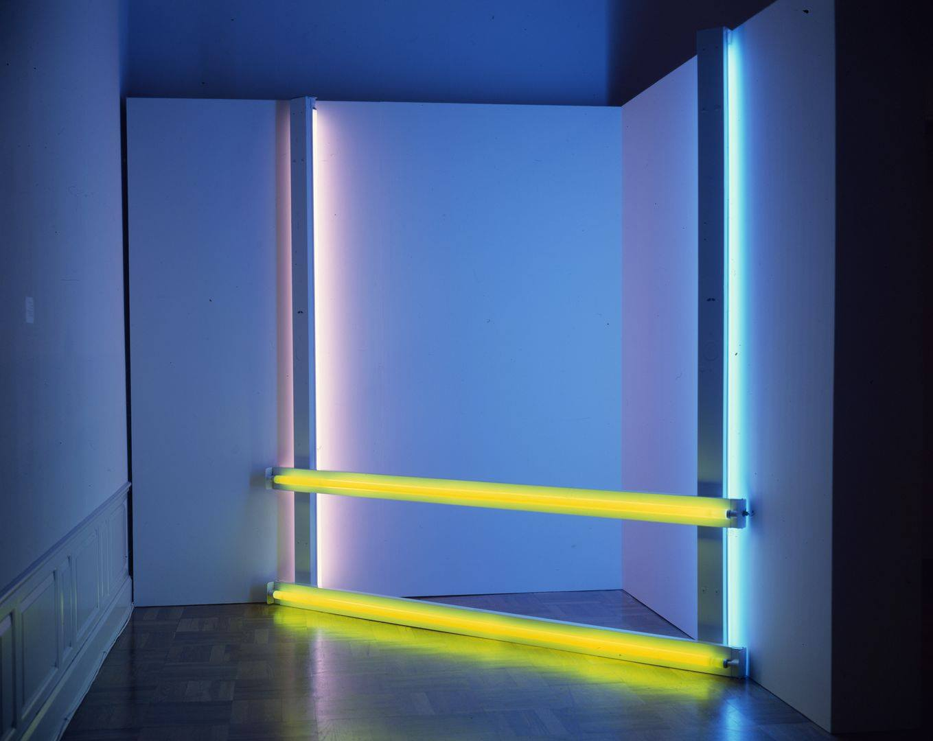 Untitled (to Donna) 2, 96 ¼ x 96, fluorescent light. An installation of fluorescent lights positioned in a corner consisting of two bright yellow lights running horizontally at floor and knee level and two fluorescent lights running horizontally at each end with the light component facing the wall. The horizontal lights are bright blue at the right and mauve at the left. All four lights cast their colors on the corner walls and floor.