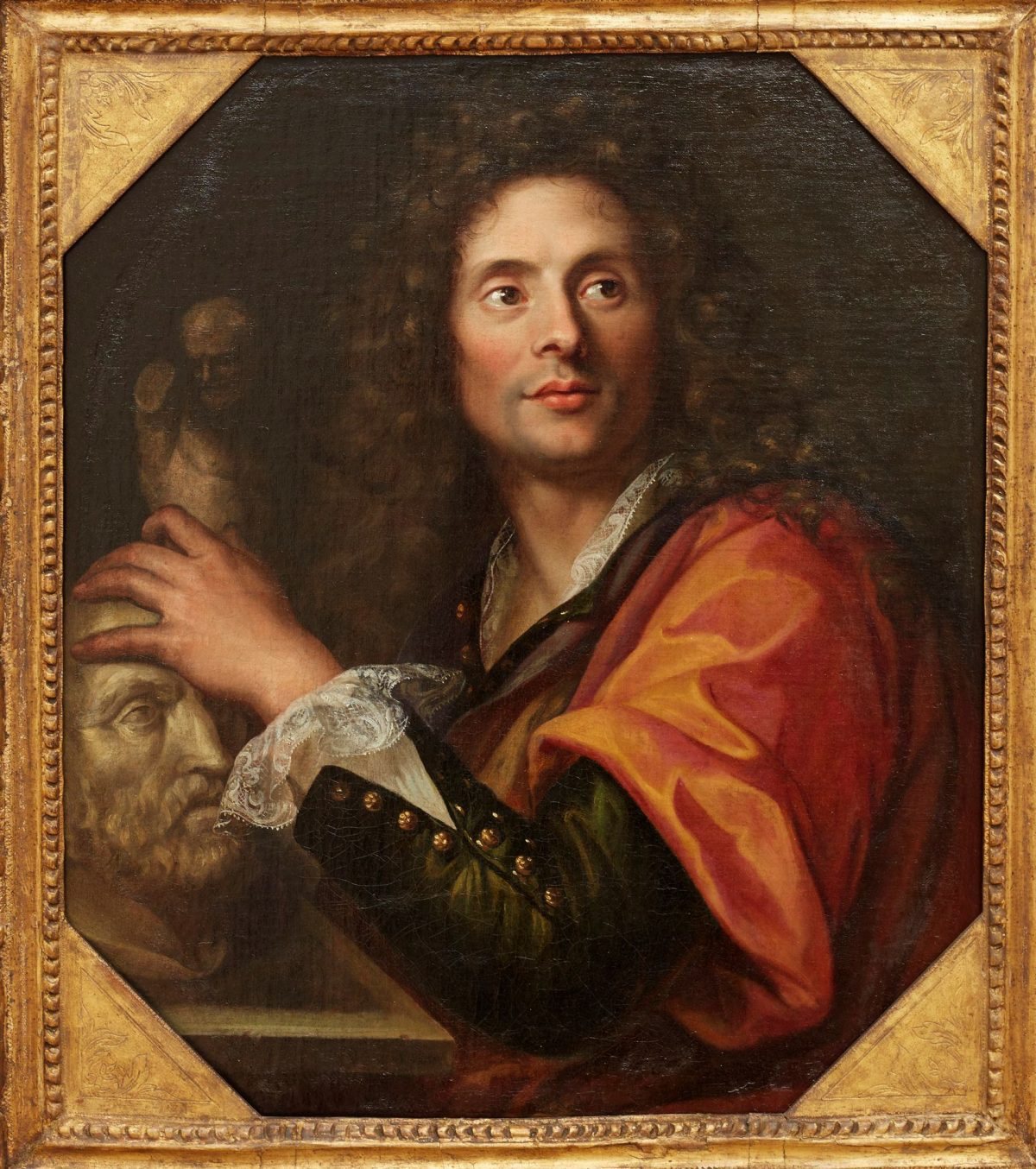 Portrait of a Sculptor, Gabriel Revel, 26 ¼ x 22 ¼, oil on canvas. A vertical rectangular portrait of a man in 17th century dress posing with sculpture. The man is depicted in three quarter view from the waist up with his shoulder turned towards the viewer. His arm crosses in front of him and his hand rests on a sculpture. His body is turned towards the left and he gazes off to the right. The man is light-skinned with large brown eyes, full lips and long, full, curly brown hair that falls well past his shoulders. He wears a brownish-black coat that is open at the throat over a white shirt with lace at the collar and cuffs. Round brass buttons line the front and cuff of the coat. Draped over his shoulder is a length of red shiny fabric. His hand rests on a bust of a bearded man while another statuette stands in the dark background. The four corners of the painting are clipped to create an elongated octagon shaped canvas.