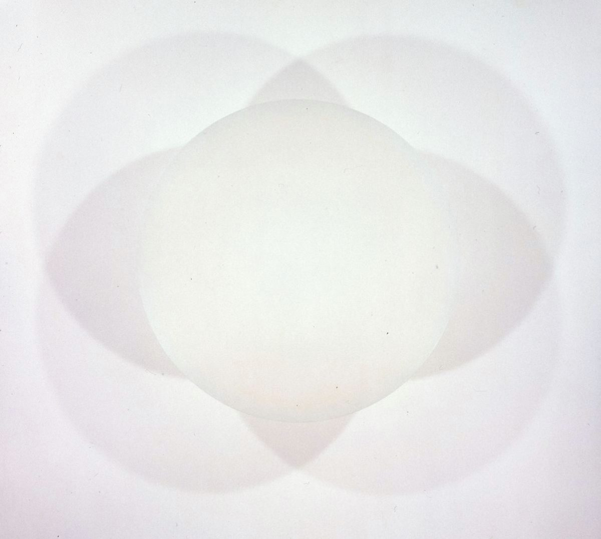 Untitled, Robert Irwin, 48 inches in diameter, spray enamel on aluminum. A photo of an ivory disc casting shadows on the wall behind it. Light shines from below causing four overlapping shadows to appear around the disc. The shadows are pale gray and deepen slightly when overlapped. The shadows and disc create one large intricate shape when looked at together or five separate simple shapes when viewed individually.