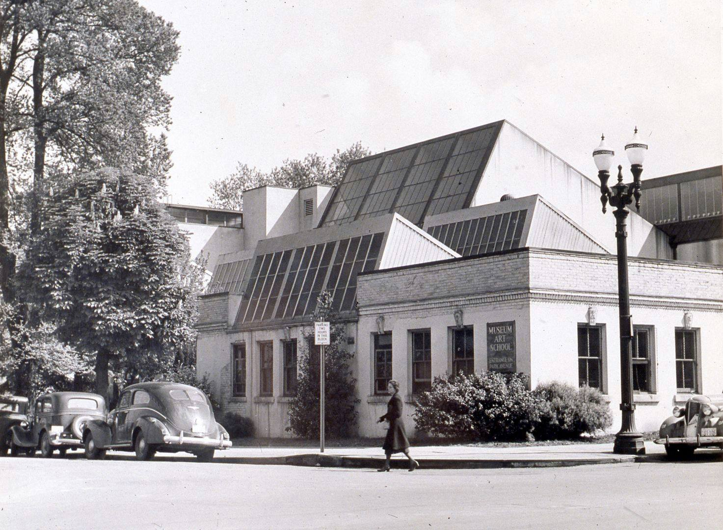 A horizontal black-and-white photograph of a building at a three-quarter view. The building is faced in light-colored masonry with seven vertical, rectangular windows facing on the left side of the building; three on the right side. Centered are three large angled skylights facing left. A twin, ornamental street lamp is visible on the corner of the street. 3 cars are parked along the sidewalk outside the building. A darkly clothed figure walks from right to center of photo crossing the street.