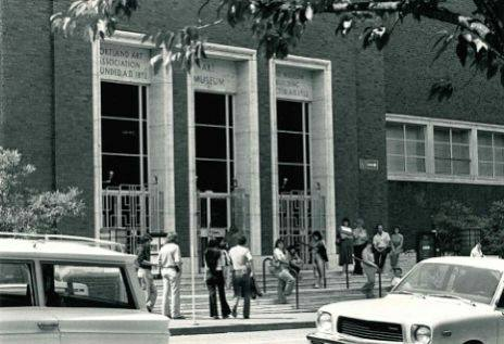 Horizontal, rectangular black-and-white photo of the front of the Museum's entrance, three vertical, evenly spaced entryways faced in light marble with 3 windows each above. 15 people are gathered on the steps, standing and sitting at ease. In the foreground 2 cars are parked along the street.
