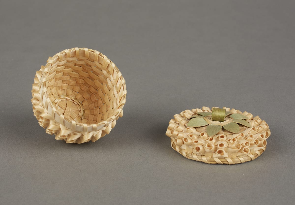 Strawberry Basket by Mary Adams (Mohawk, Canadian), 2 inches x 2 inches, ash splints and commercial die. This tiny basket with a lid is a natural golden color overall and topped with a decorative loop handle that is dyed green to imitate leaves and a stem. The whole basket has a bumpy texture due to the weave of the materials. The weave creates rows of small looping circles that hug the surface with the open ends of the loops facing outward. They are tilted slightly downward on the body of the basket and more upward on the lid. Around the edge of the lid, where it meets the body of the basket, the weaving materials are bound together with a splint spiralling around the edge. It looks very much like an unripe strawberry with the dark shadowy centers of each of the loops resembling rows of seeds.